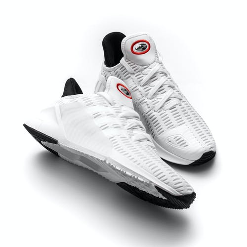 From above of sportswear with white breathable surface with rubber inserts and laces and two colored soles for good workout placed against white background
