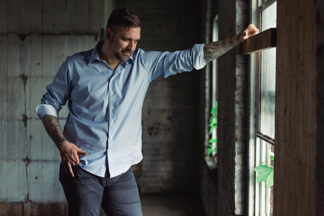 Smiling Man Standing Near Window Looking Straight