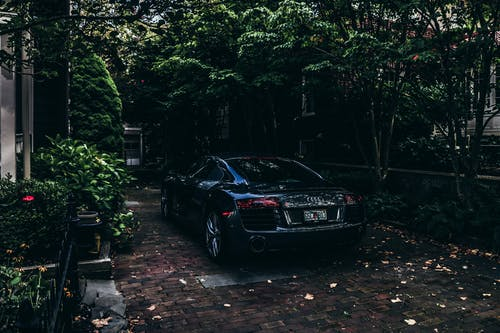Black Audi Sedan Parked on Pavement Near Trees