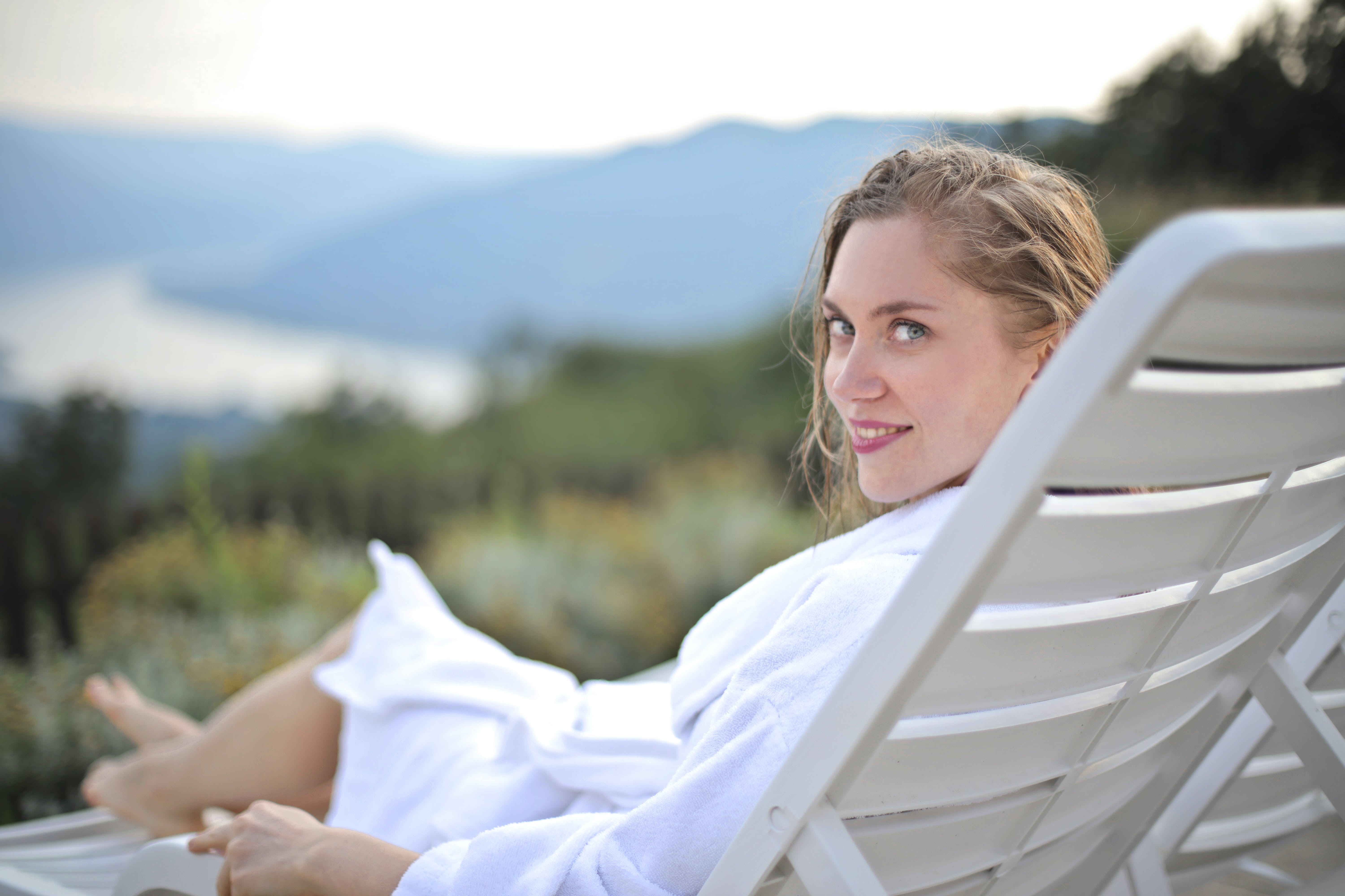 Selective Focus Photography of Smiling Woman Wearing White Bathrobe Lying on Pool Chair