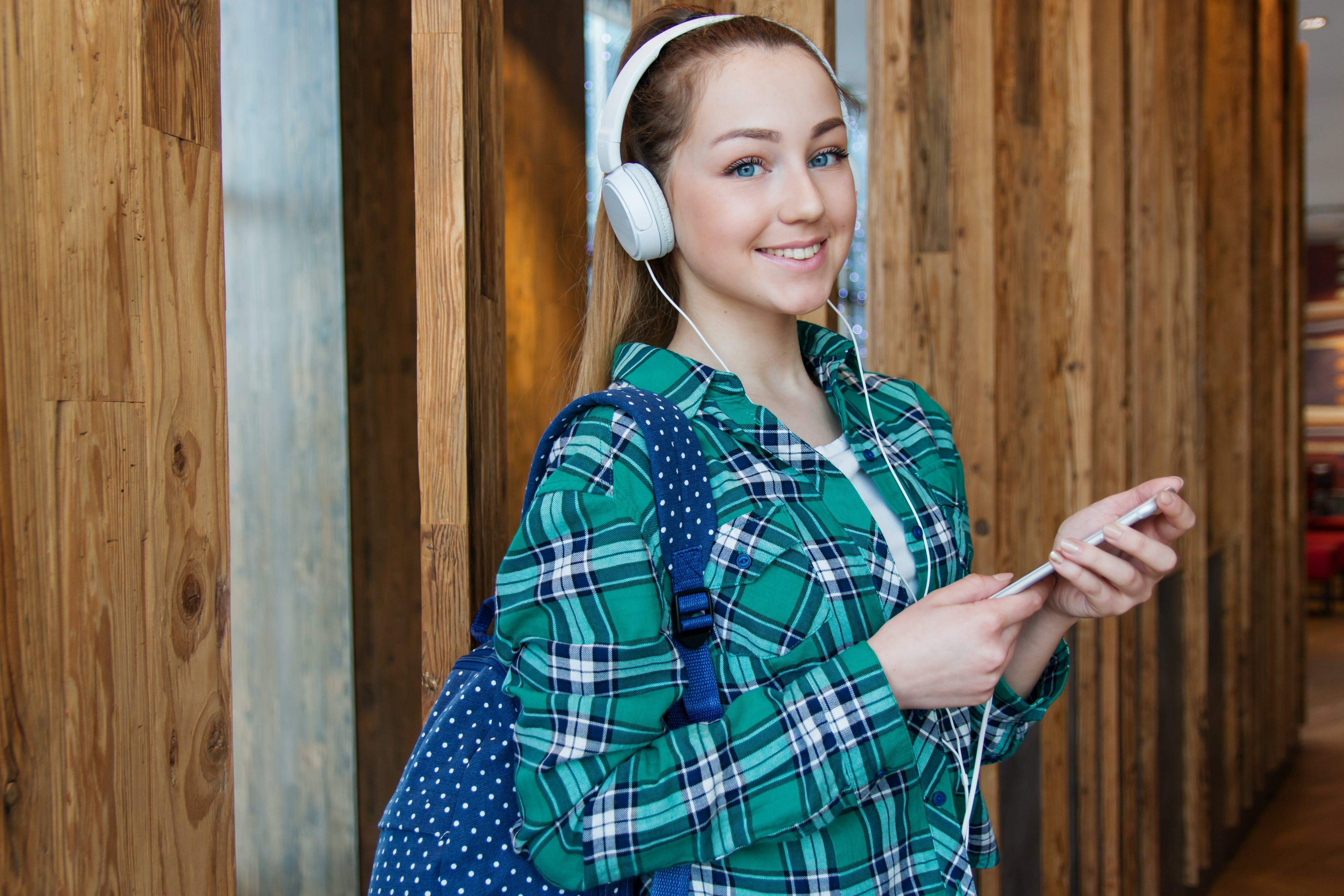 Woman in Teal, White, and Black Plaid Dress Shirt Standing Beside Brown Wall