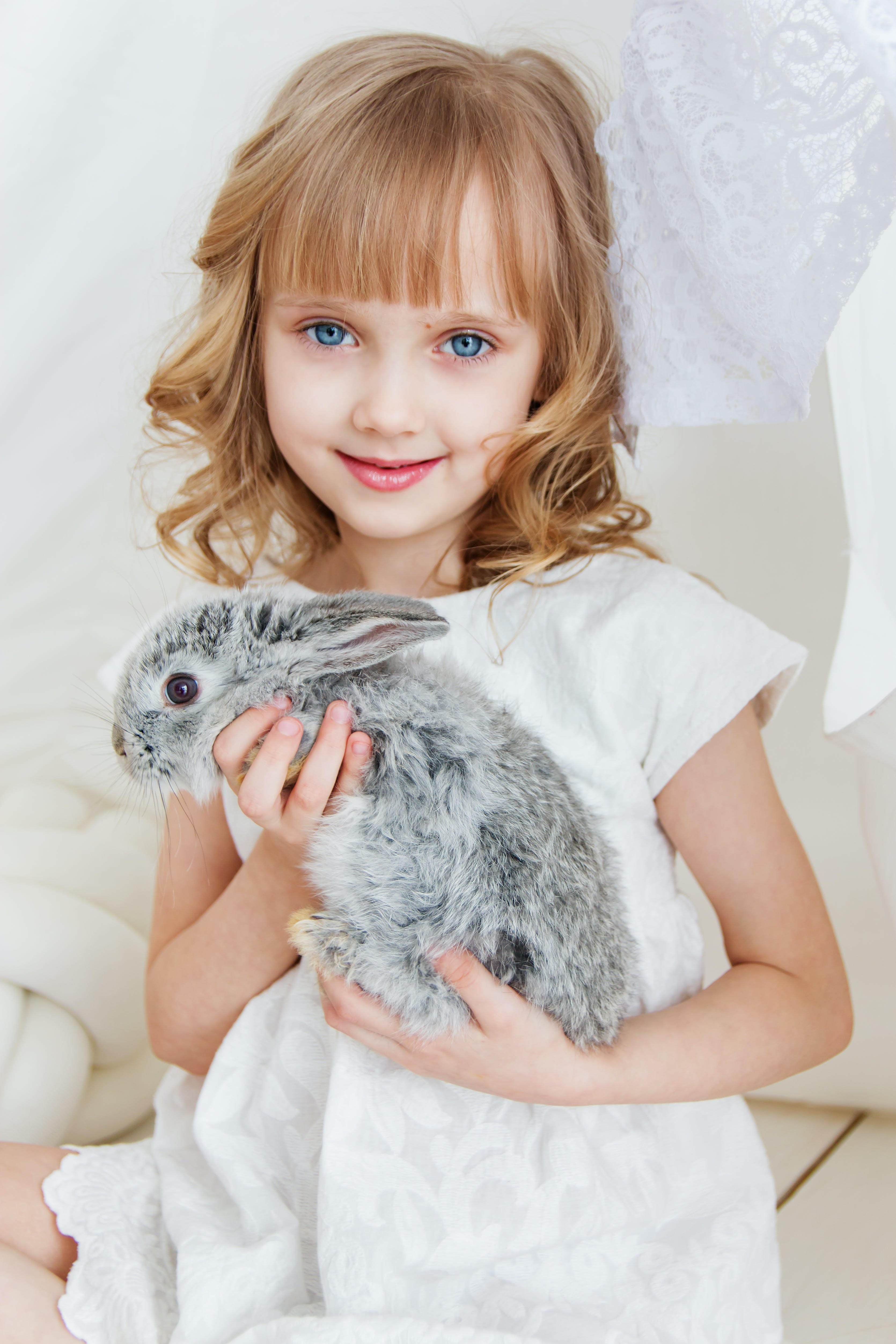 Smiling Girl Holding Gray Rabbit