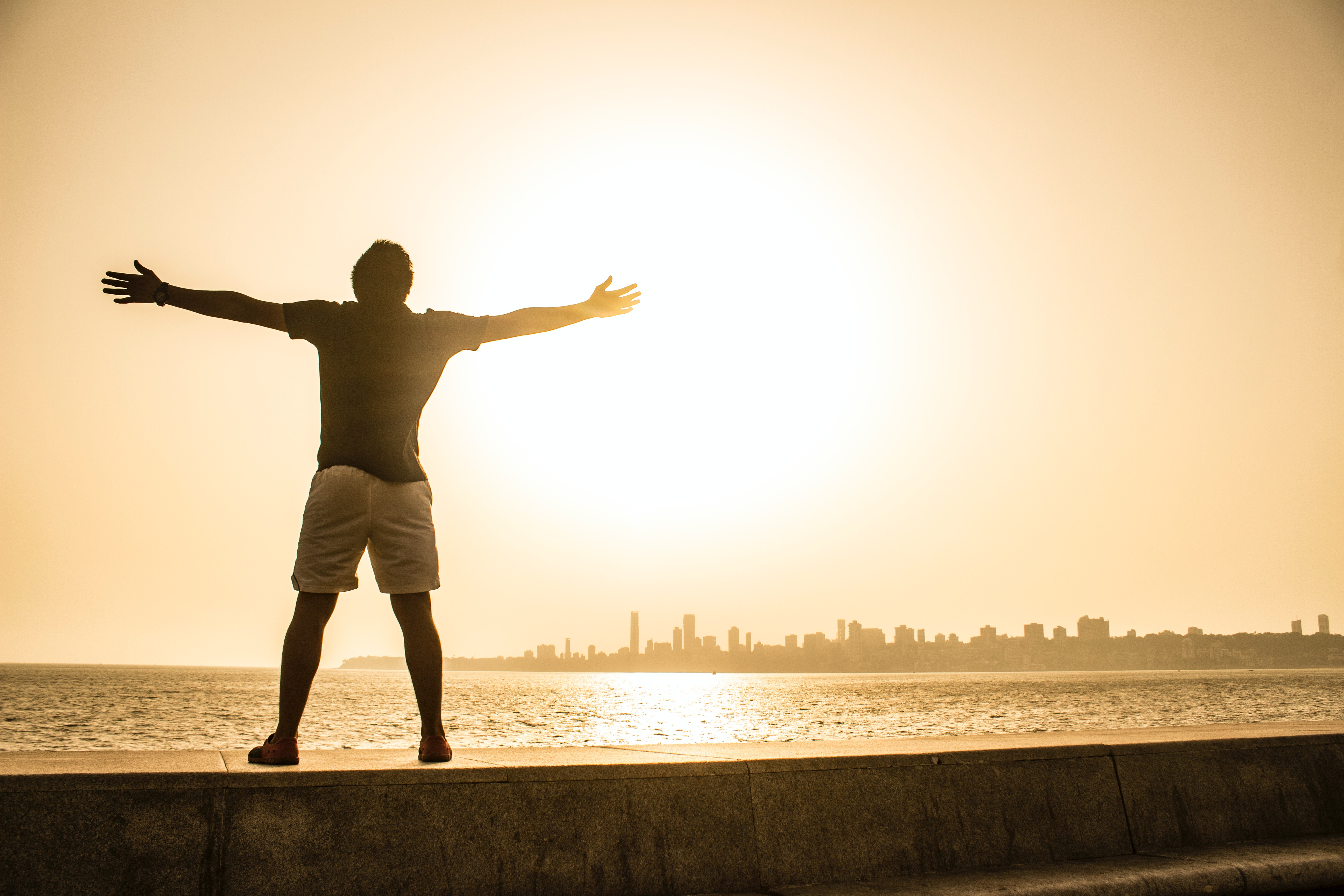 Free Spreading Pics man standing on ledge while spreading arms · free stock photo