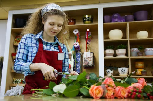 From below of positive female florist in apron and hairband using scissors for cutting low parts of rose branches placed on table in workspace against shelves with flower pots and decorations for presents