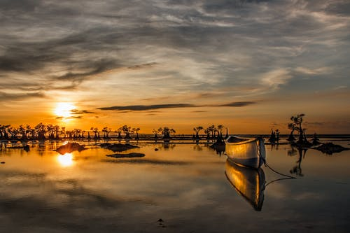 Wooden Boat on Water Under Golden Sky
