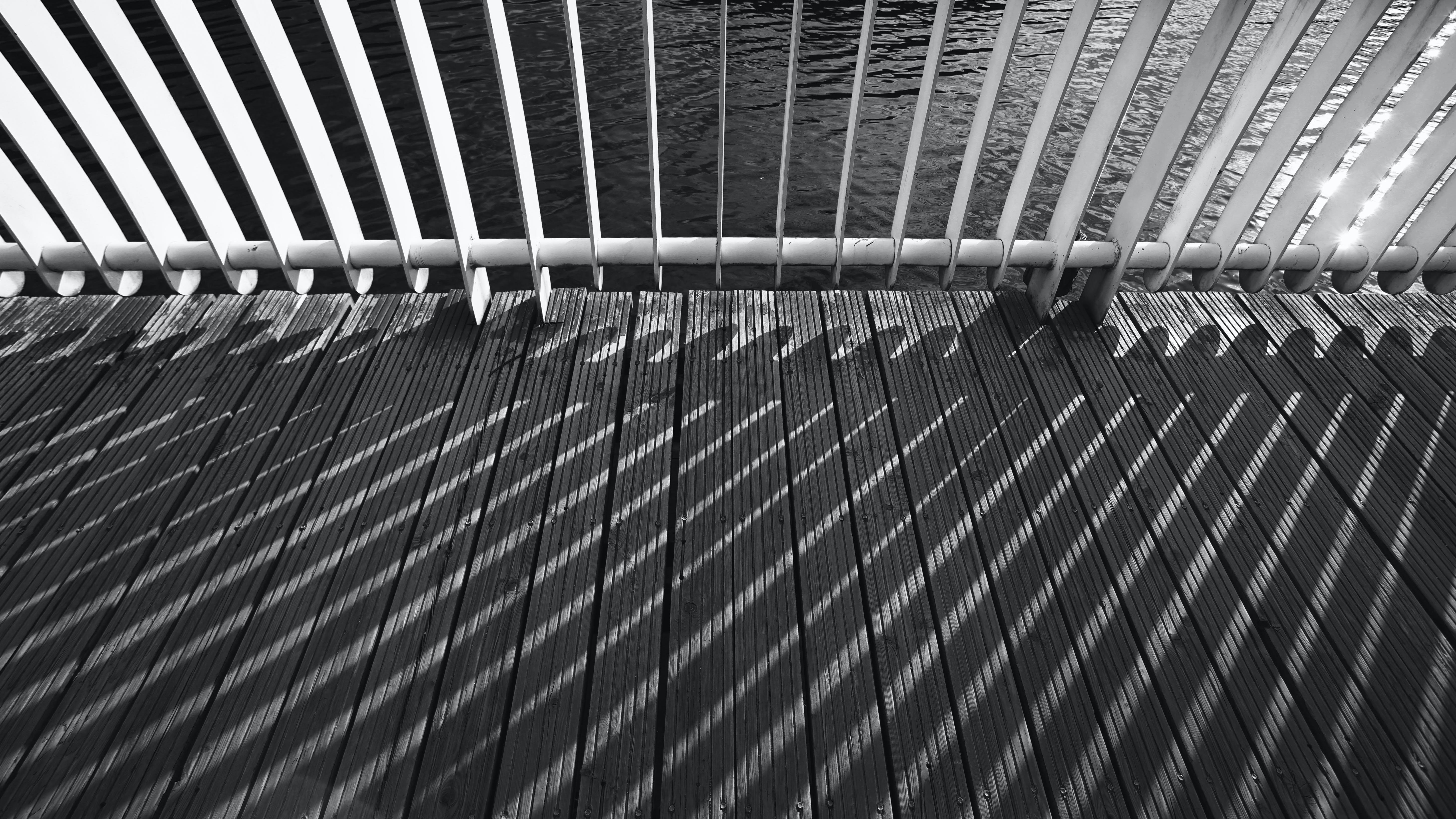 Grayscale Photo of Shadow of Metal Railing