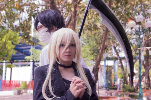 Male and Female Anime Character Cosplay With Scythe Beside Tree