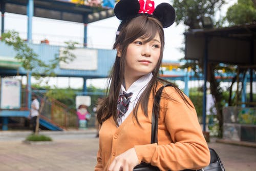Woman Carrying Black Bag and Wearing Minnie Mouse Headband