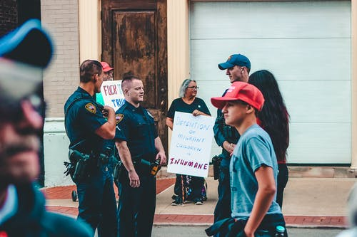 Police Standing Near Woman and Man Holding Up Signage