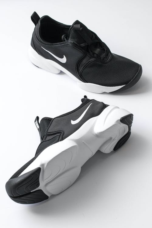 From above of sports shoes pair with black breathable surface and white soles comfortable suiting on feet placed on white background