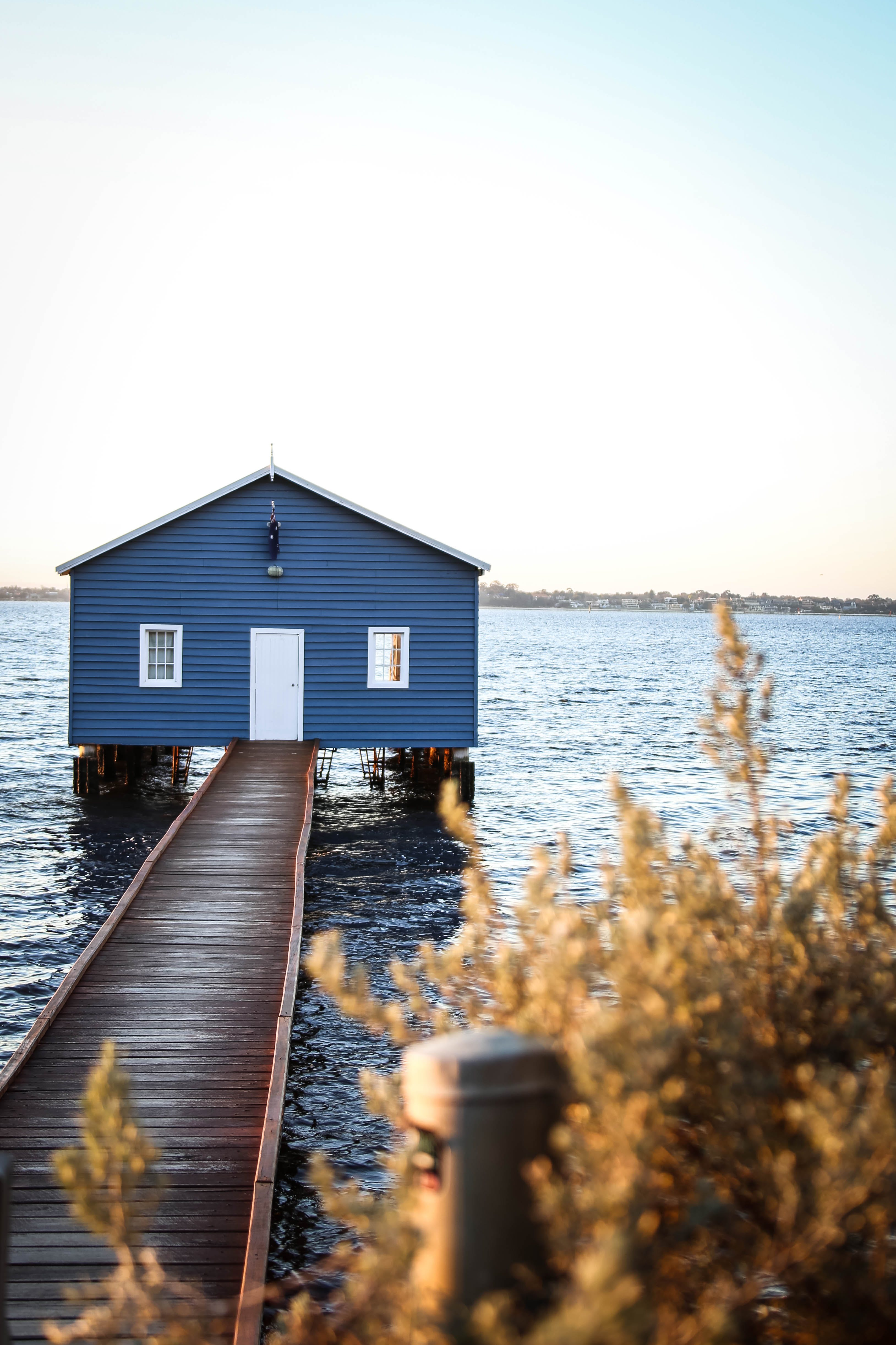 House With Dock on Body of Water Under Blue and White Sky