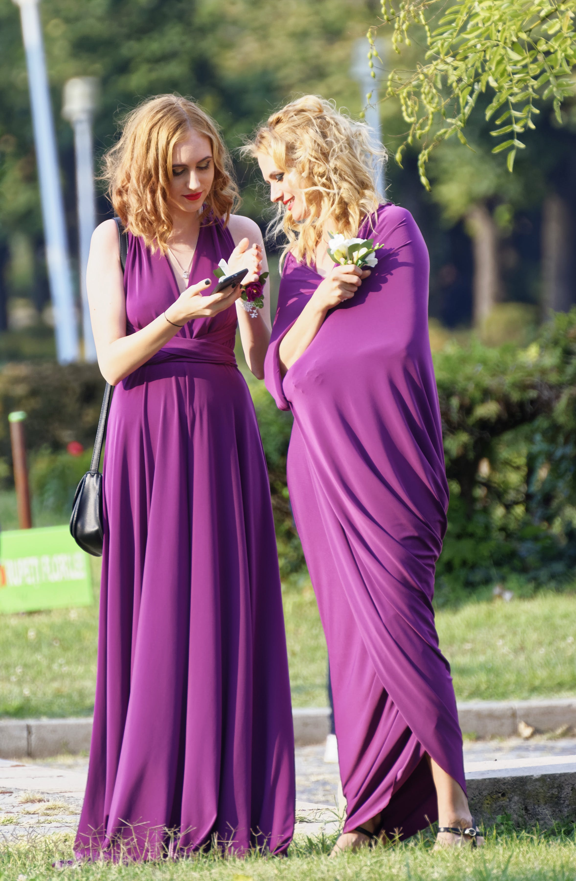 Two Women Wearing Purple Dresses on Grass Field