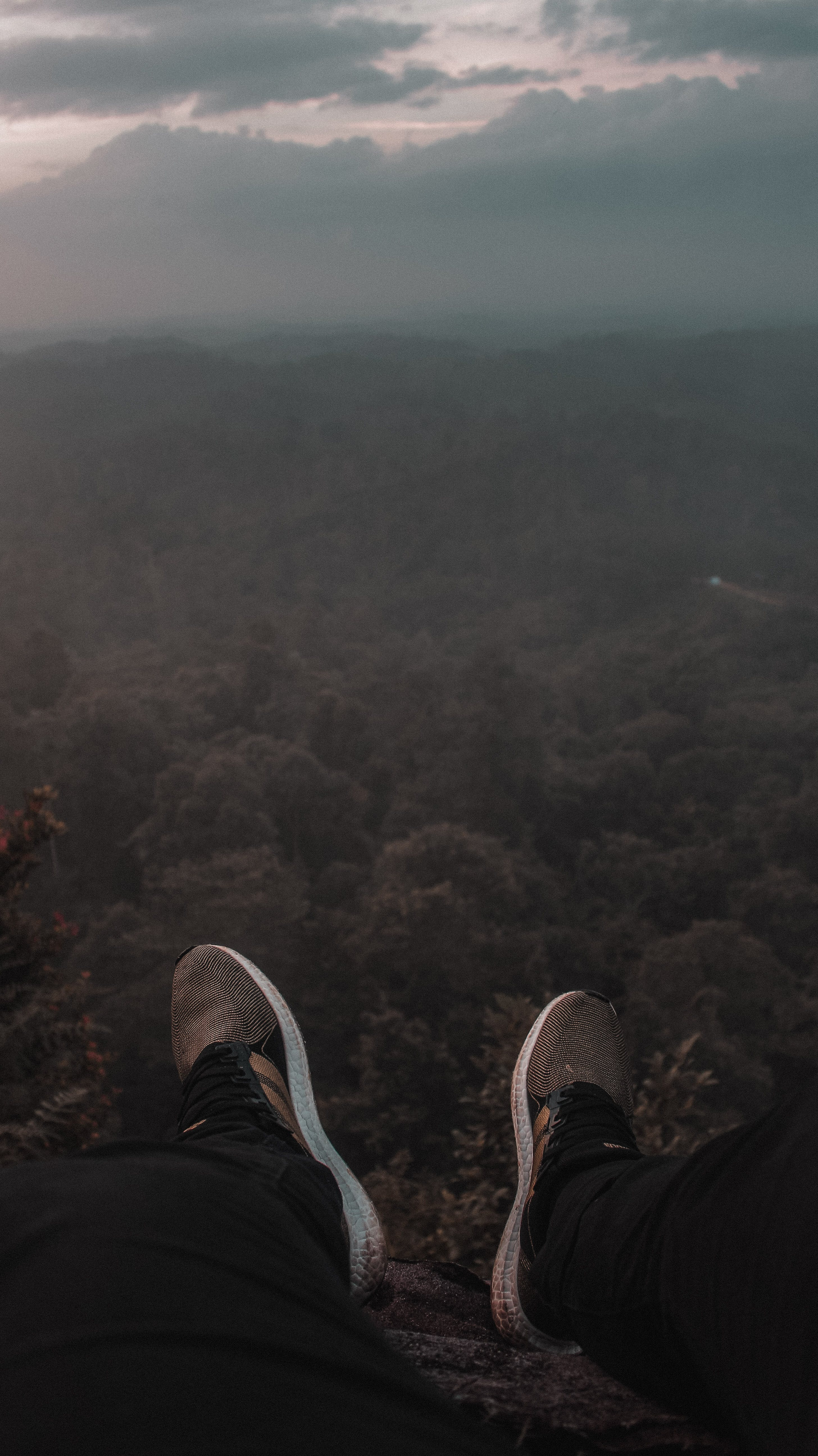 Person Sitting on the Edge of Mountain