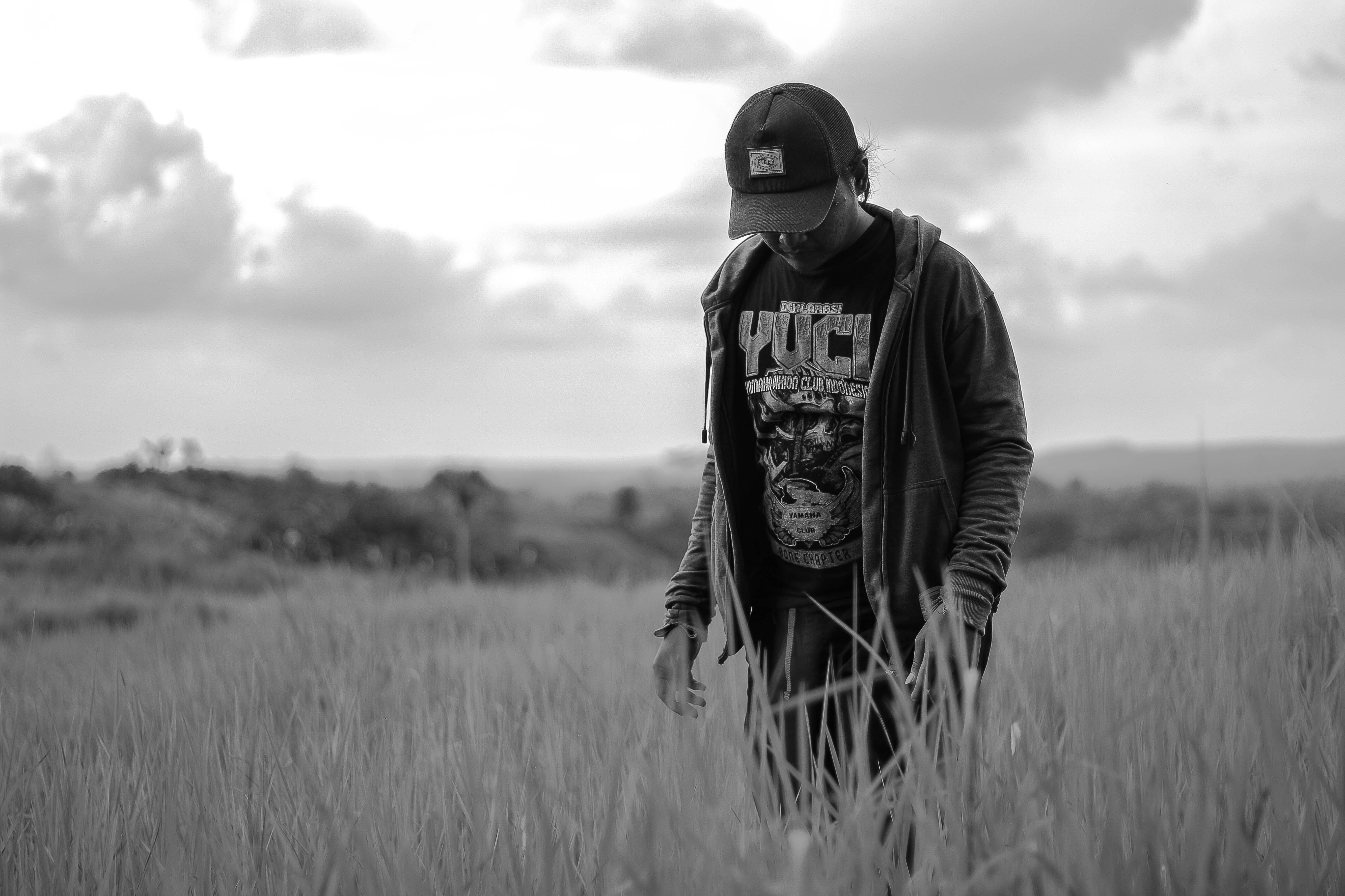 Monochrome Photo of Man On Grass Field