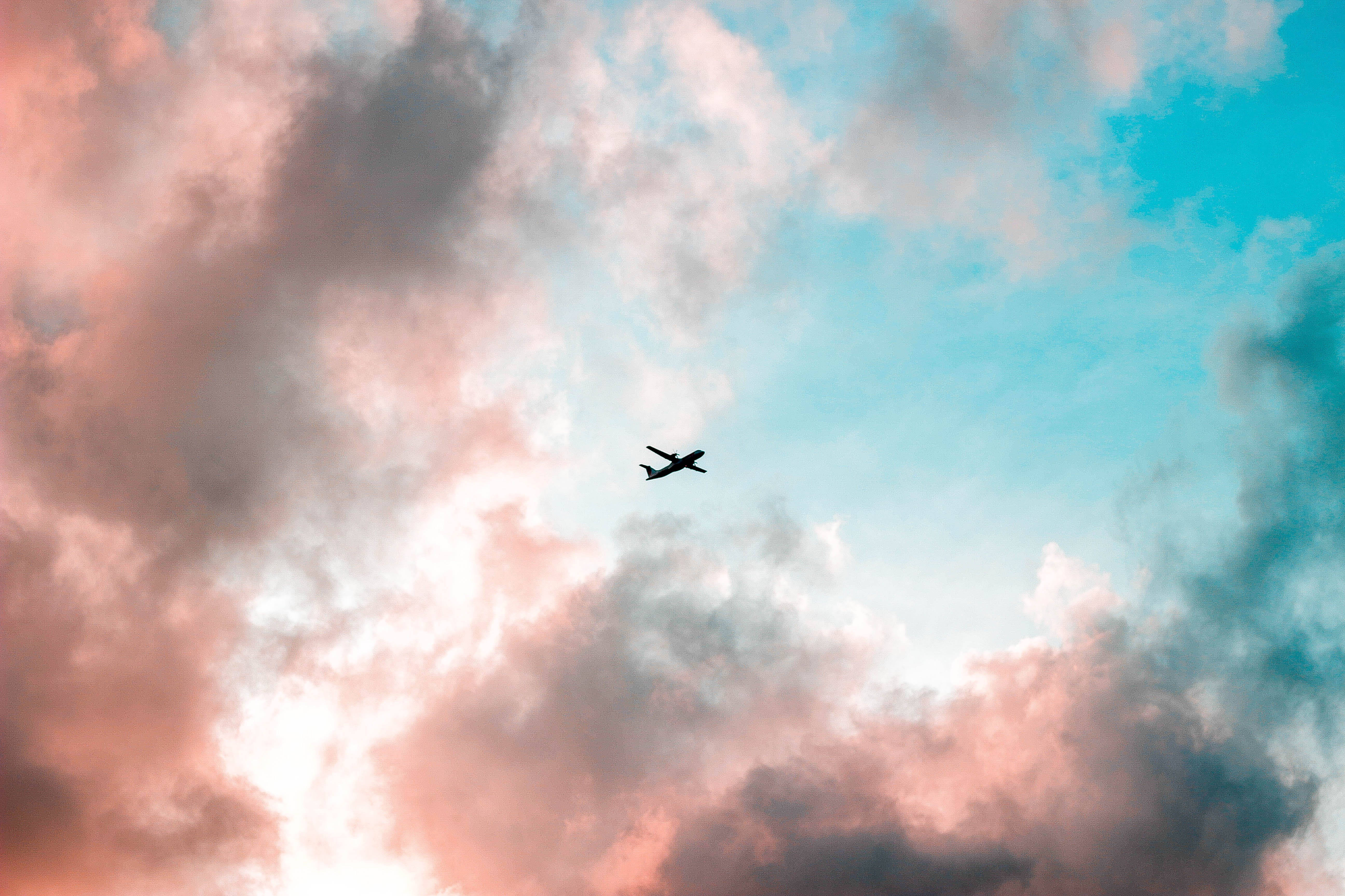 Silhouette of Airplane Under Cloudy Sky