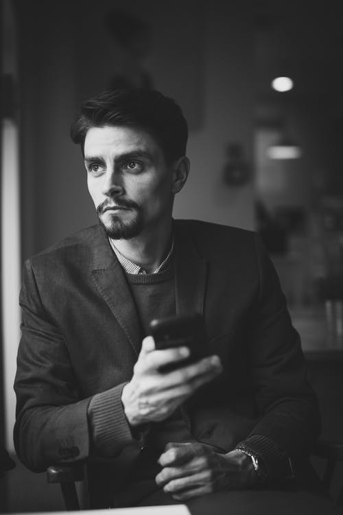 Grayscale Photography of Man Holding Smartphone