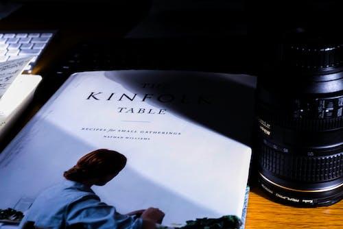 White Book Beside Camera Lens