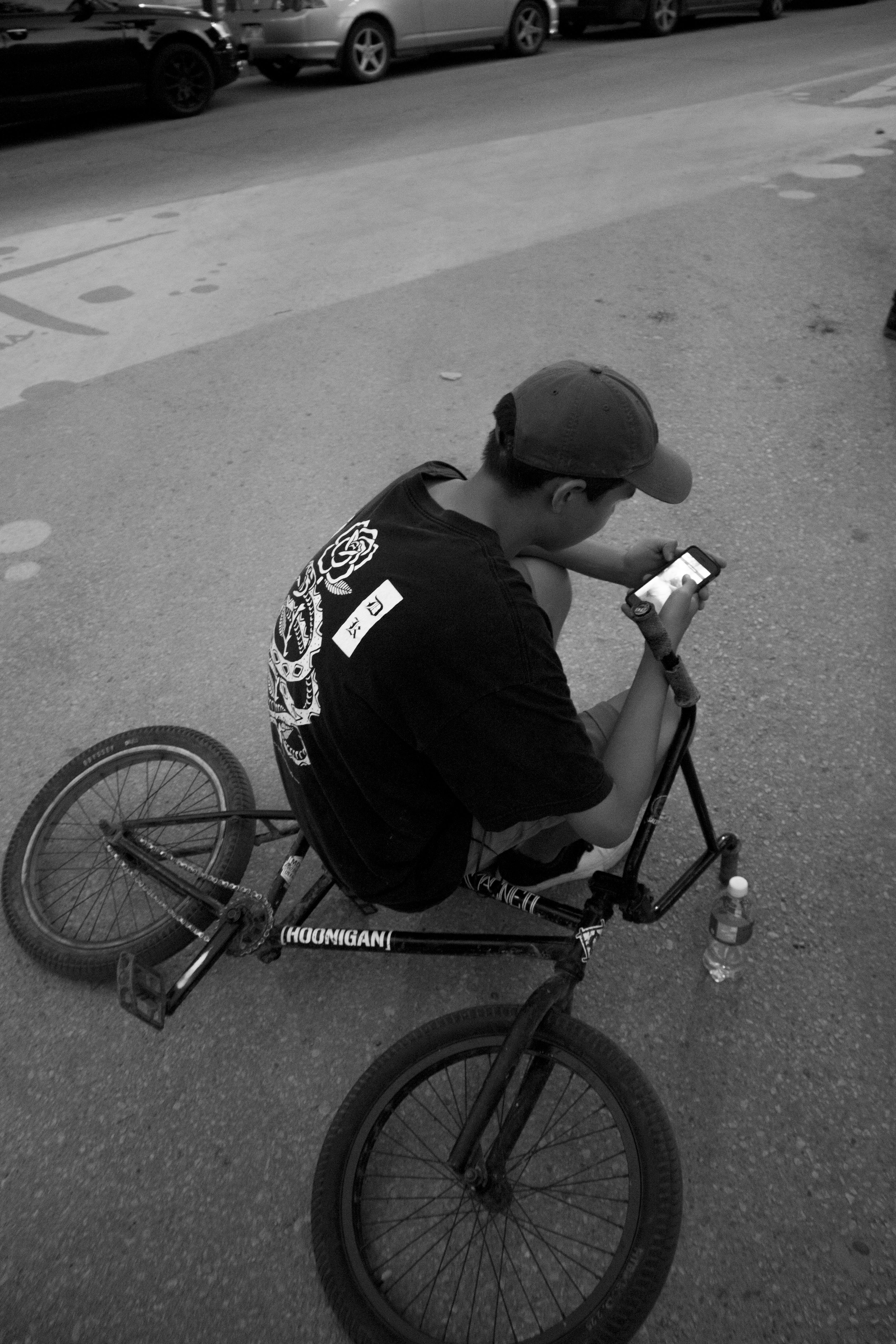 Free stock photo of bike, black and white, boy, cell phone