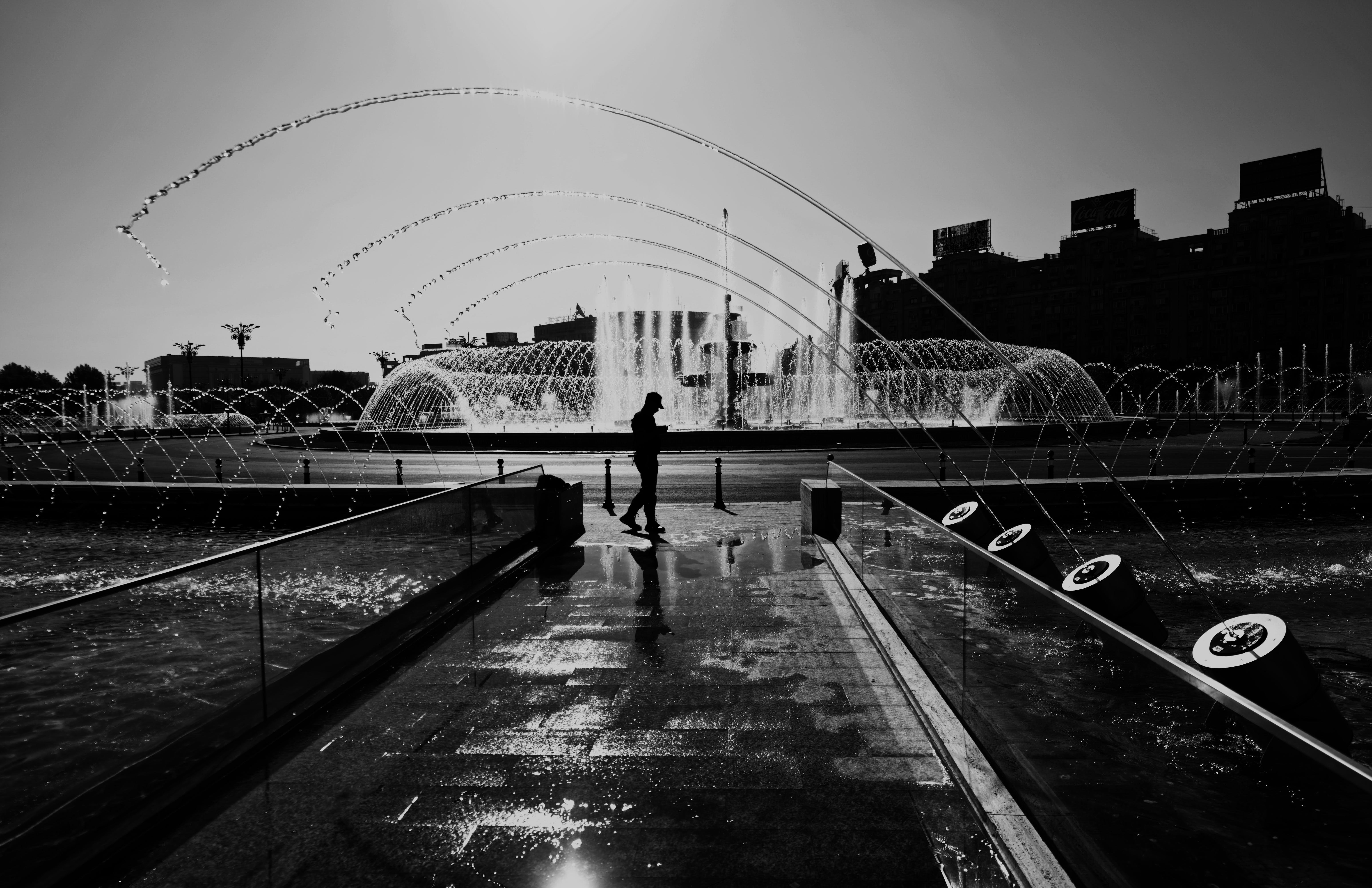 Grayscale Photography of Man Standing Near Fountain