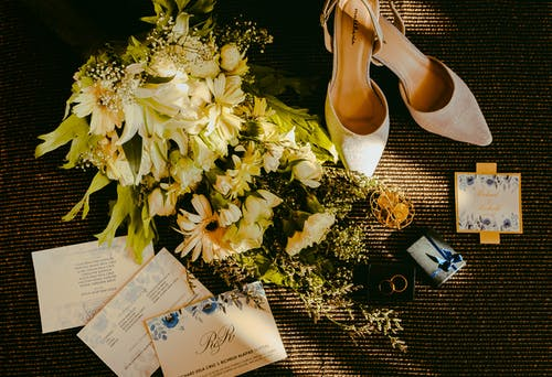 Pair Of Beige Shoes Beside Bouquet