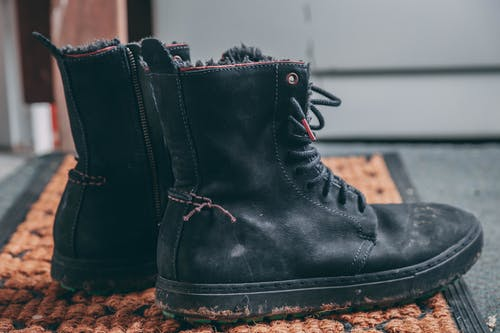Pair of Black Lace-up Boots on Area Rug