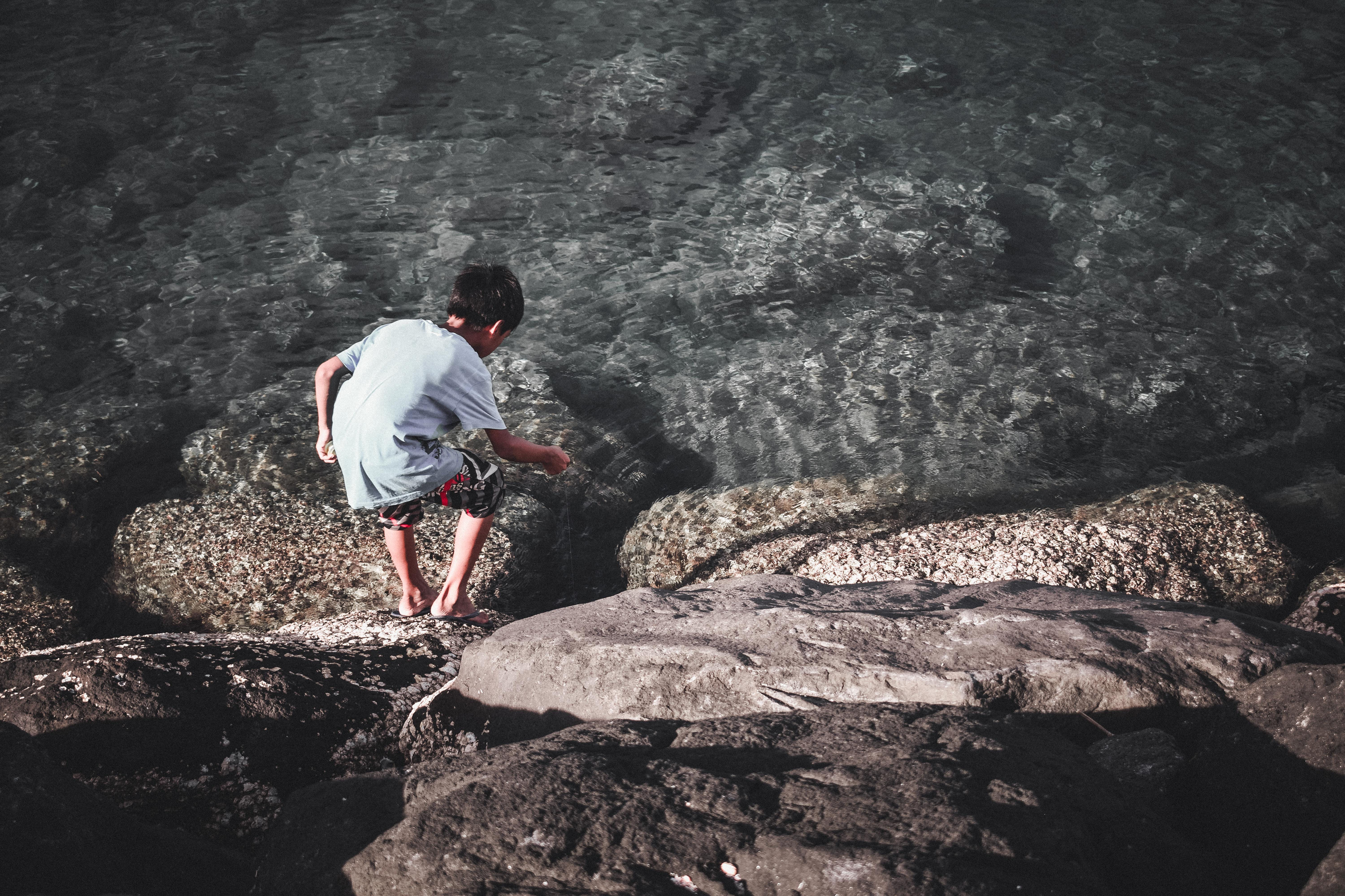 Boy Playing With Stick Near Water