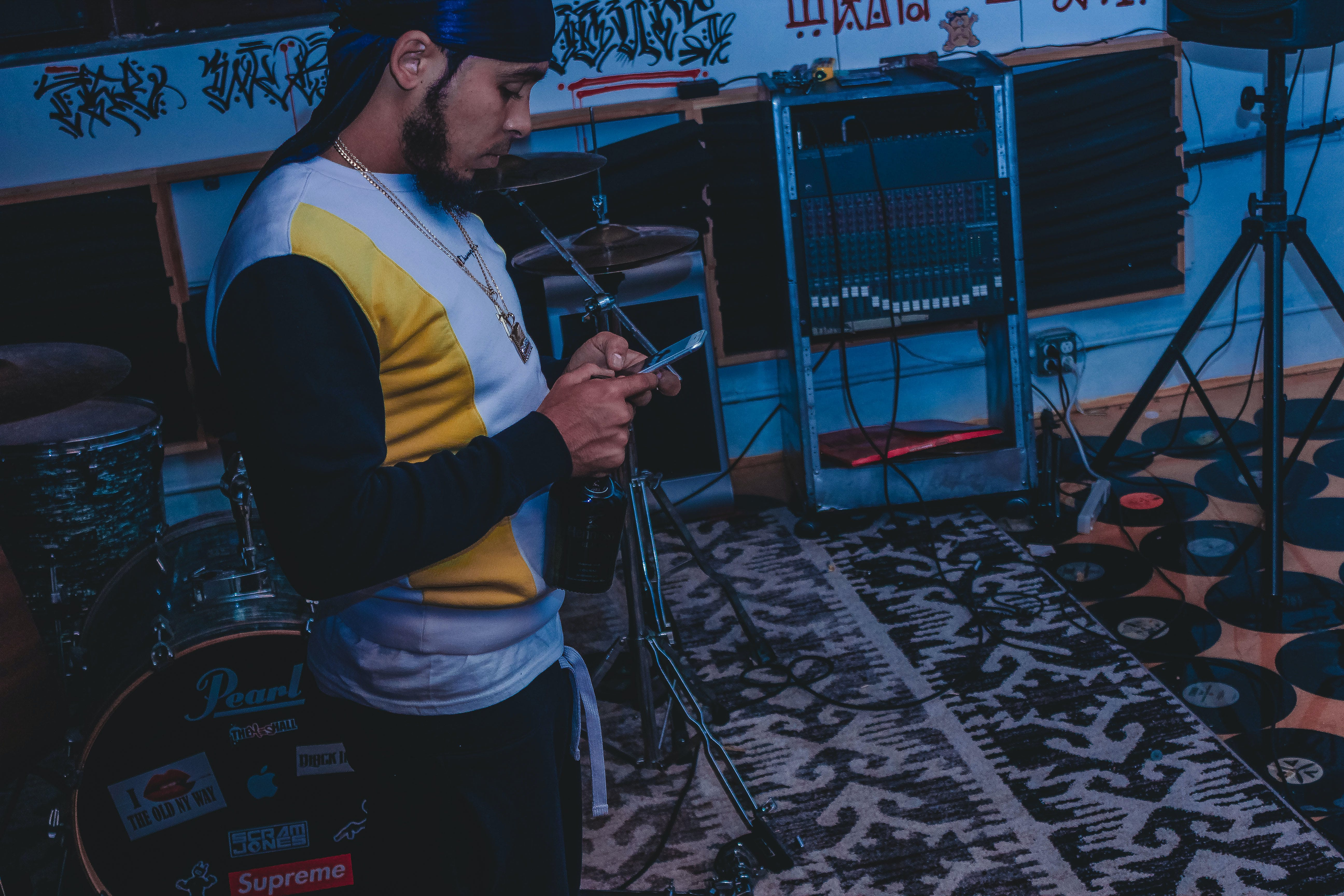 Man Standing Beside Black Pearl Drum Holding Smartphone