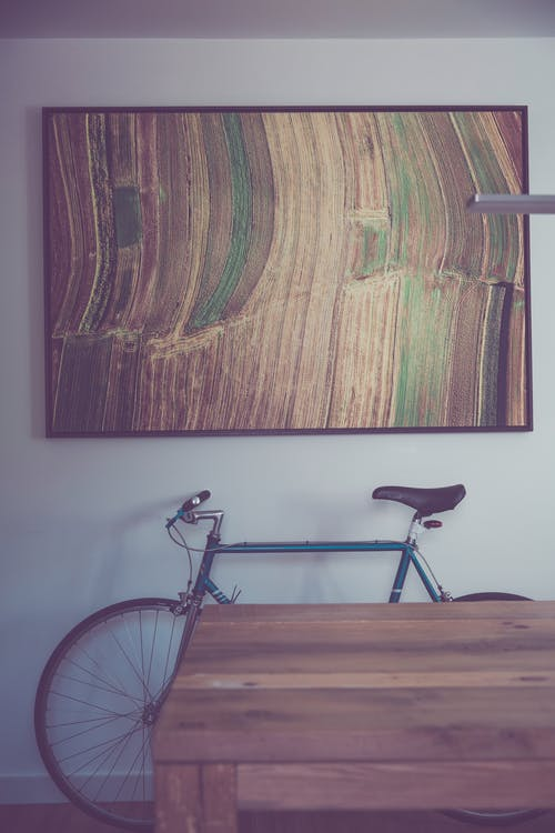 Black and Gray Bicycle on Brown Wooden Floor