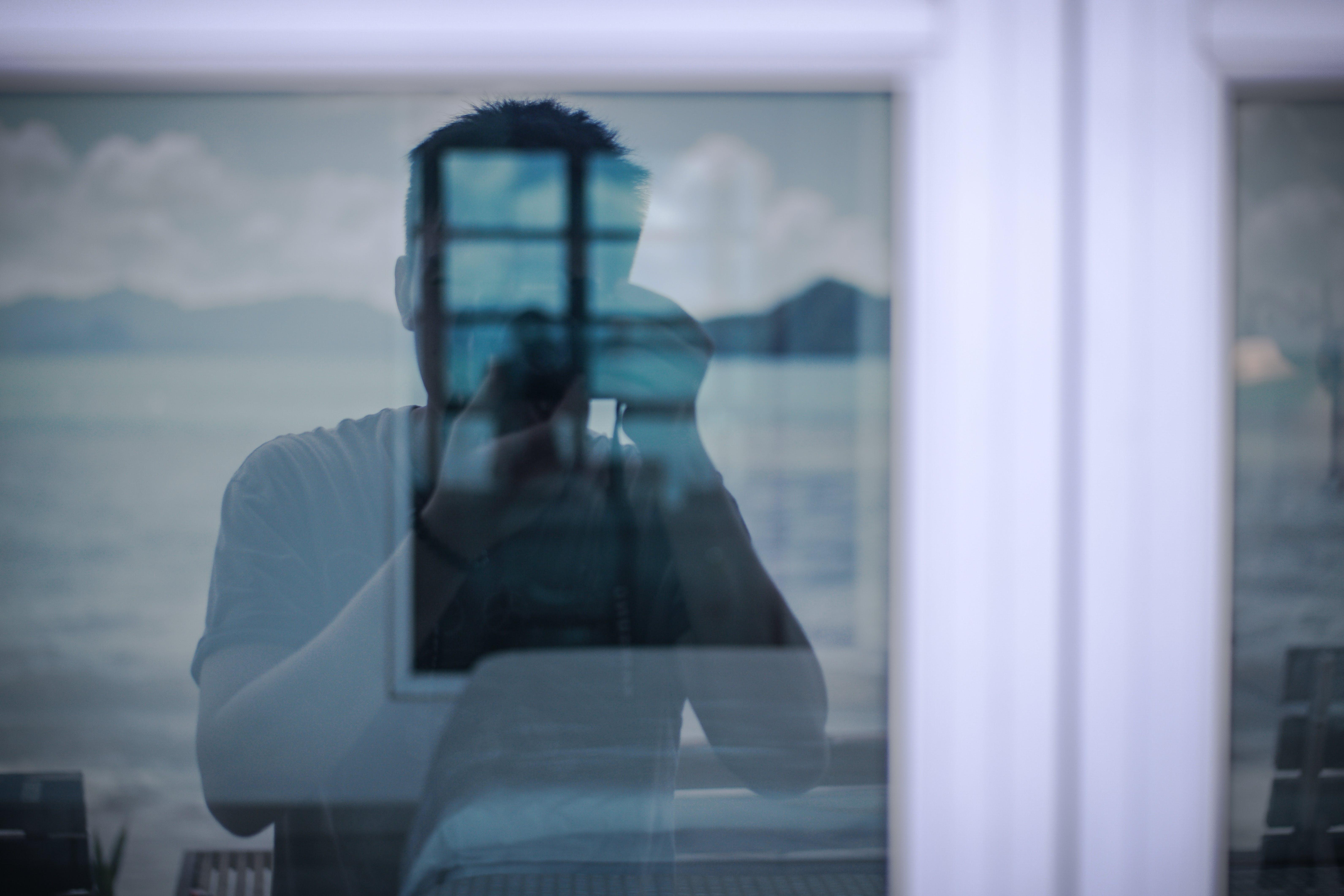 Man Taking Photo of a Windowpane