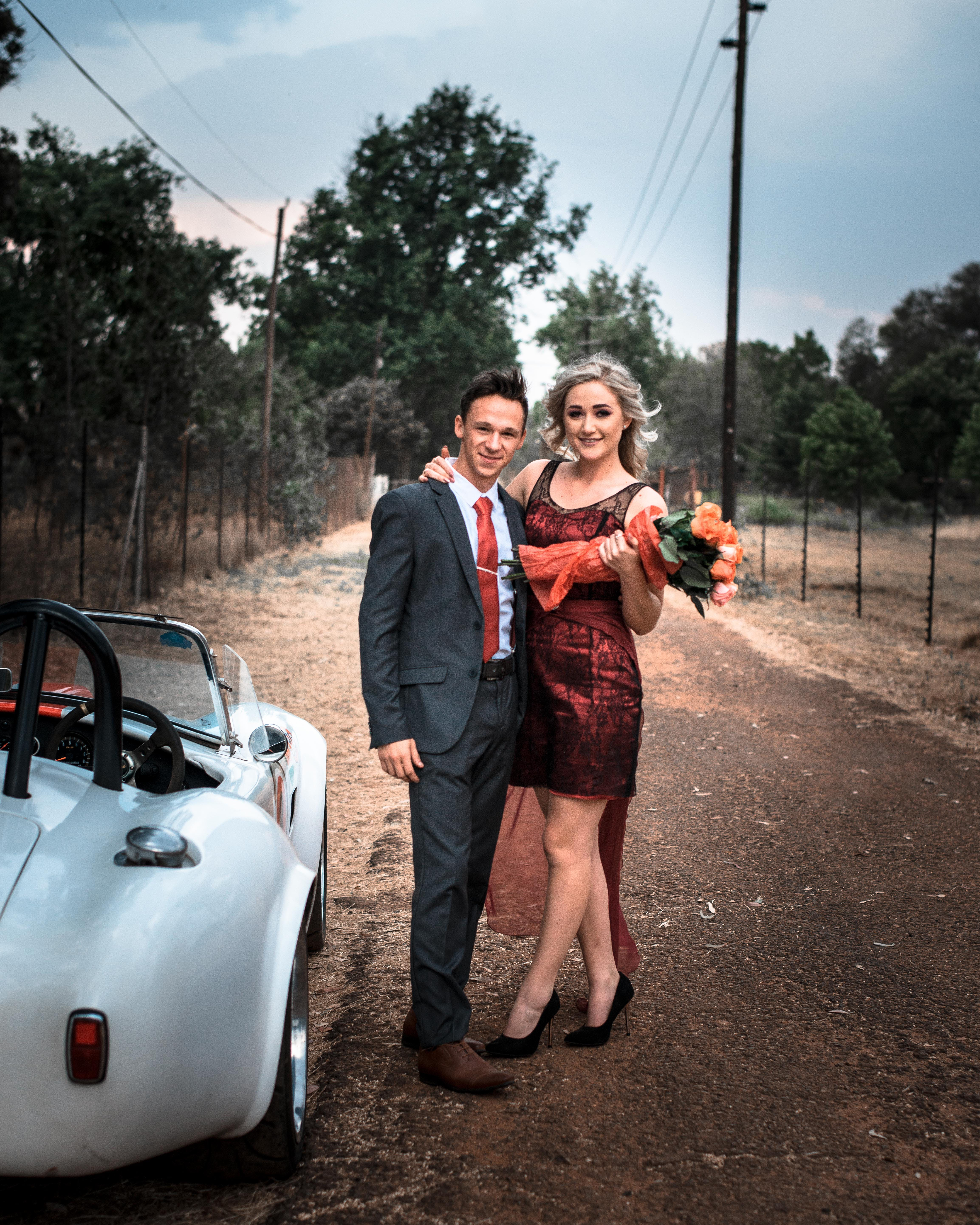 Man and Woman Taking Photo Beside White Coupe