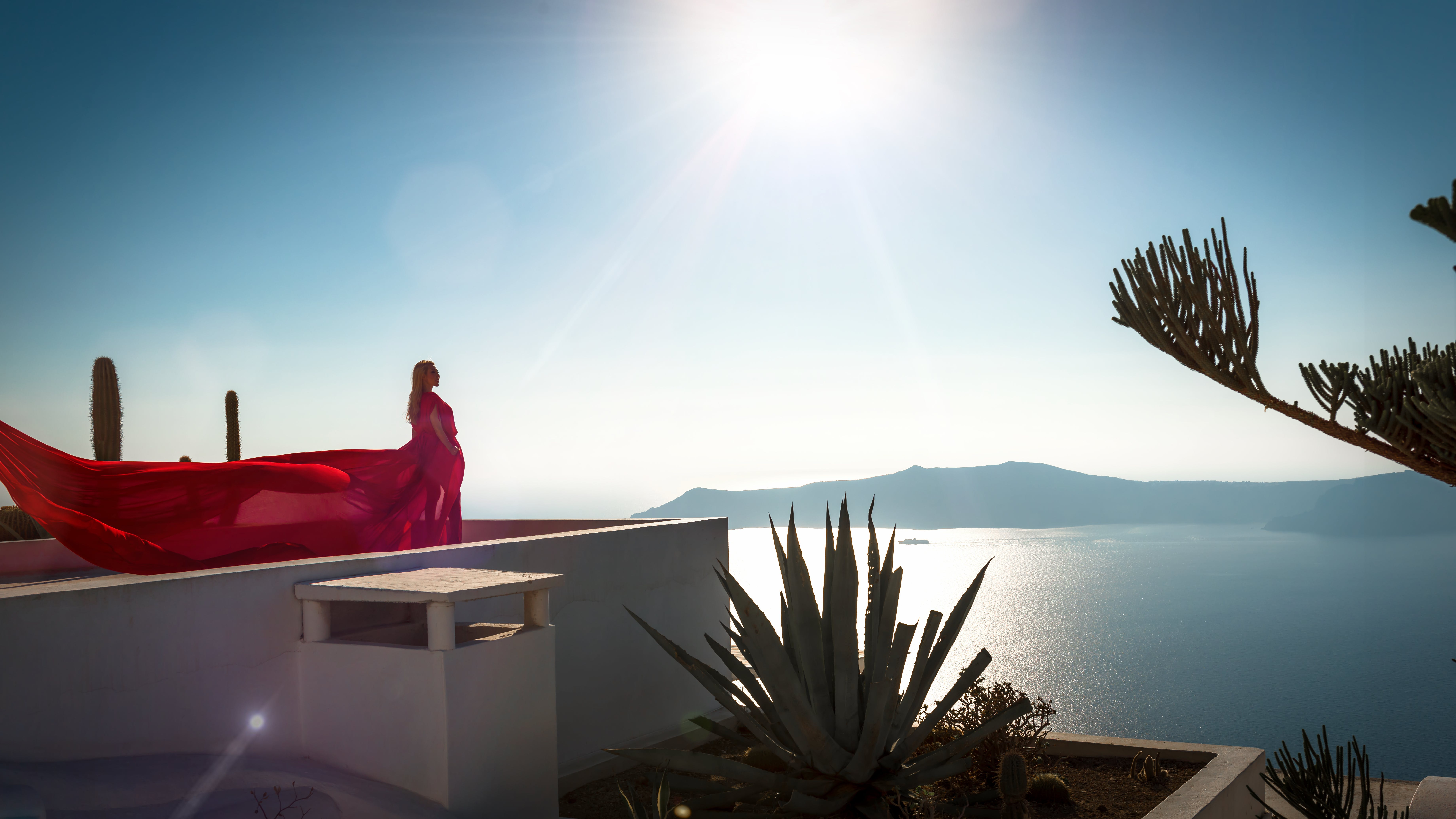 Woman Wearing Red Long Dress Standing at Rooftop of Building Facing Ocean