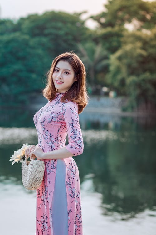 Woman Standing and Doing Pose Beside Lake