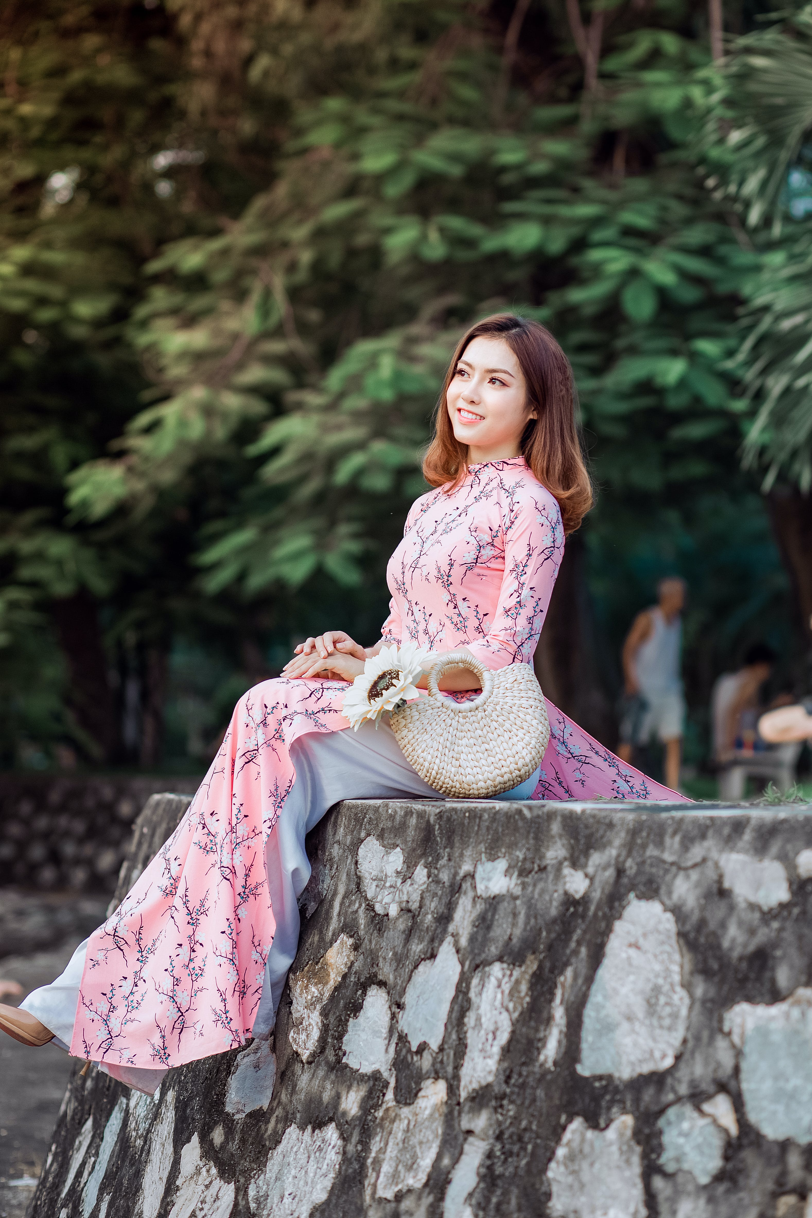 Woman in Pink Maxi Dress Sitting on Gray Wall