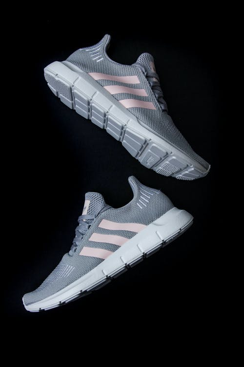 Top view of stylish known sports shoes with gray laces and breathable surface with pink strips and white soles for comfortable training on black surface