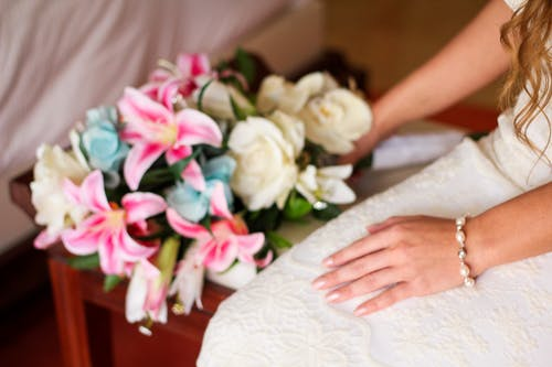 Woman Wearing White Bridal Gown While Holding Assorted-color Bouquet Flowers