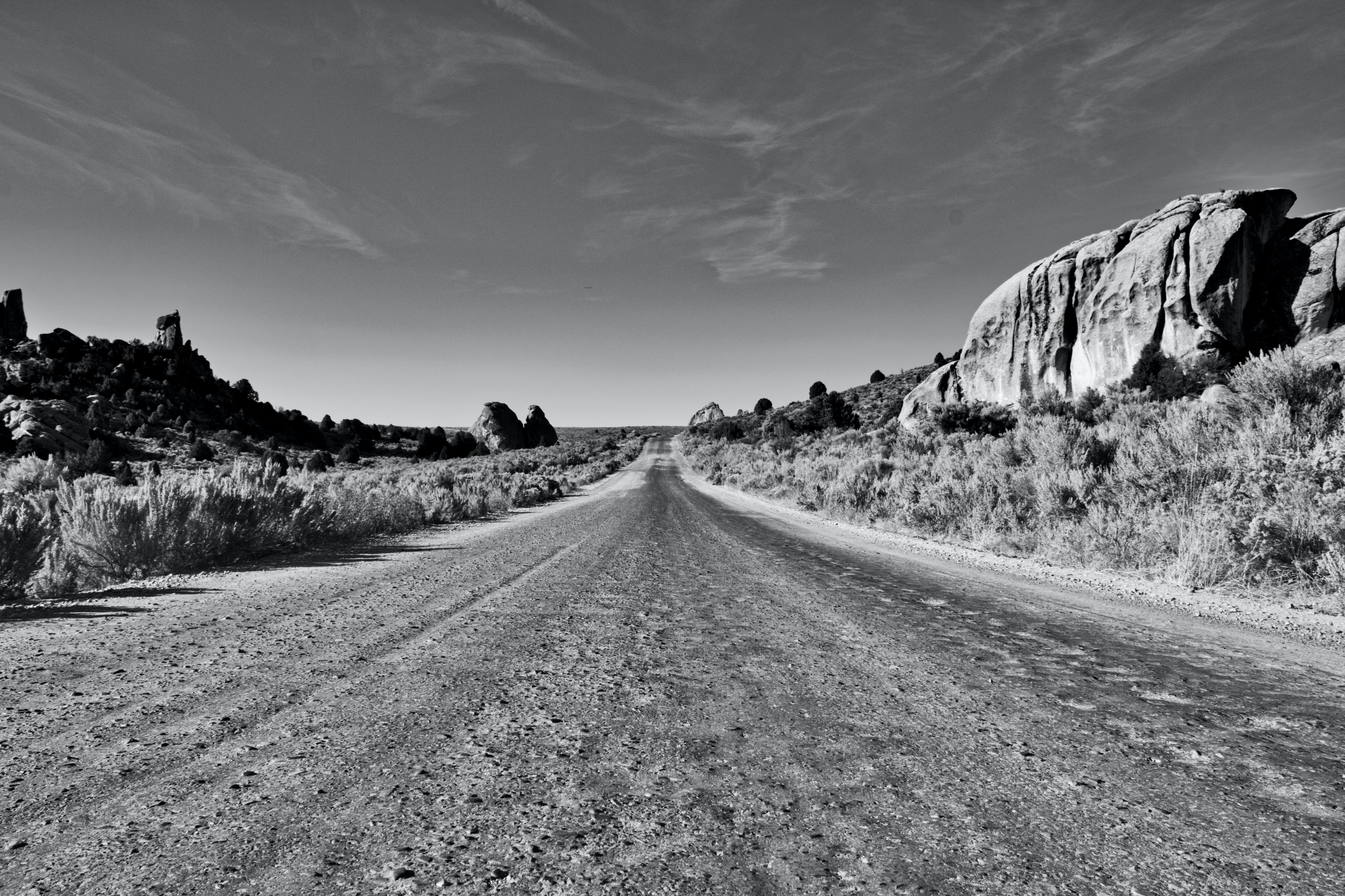 Grayscale Photography of Empty Soil Road Under Cloudy Skies