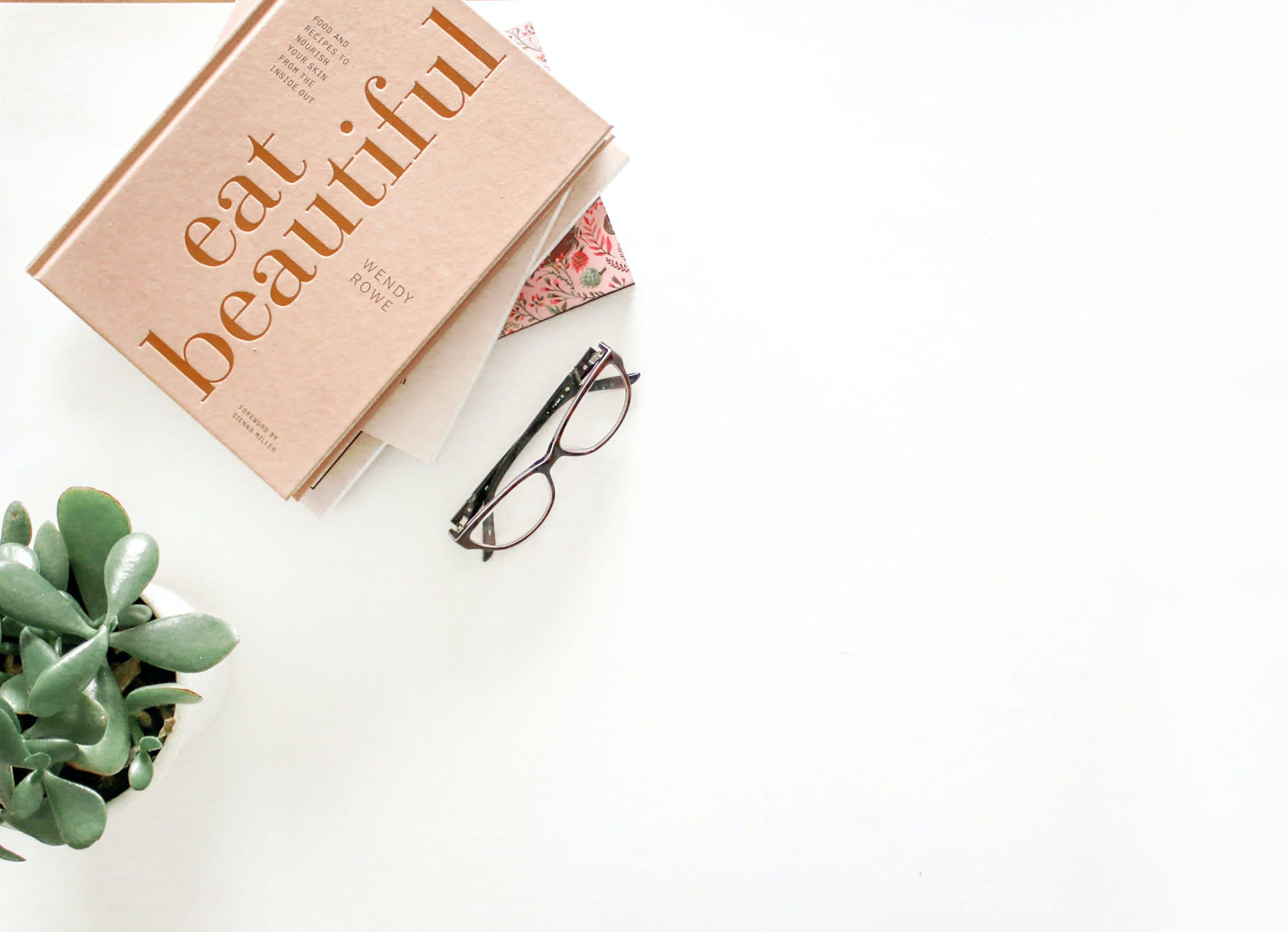 Brown Framed Eyeglasses Beside Eat Beautiful Book