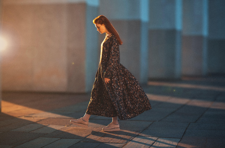 Woman Walking on Gray Surface