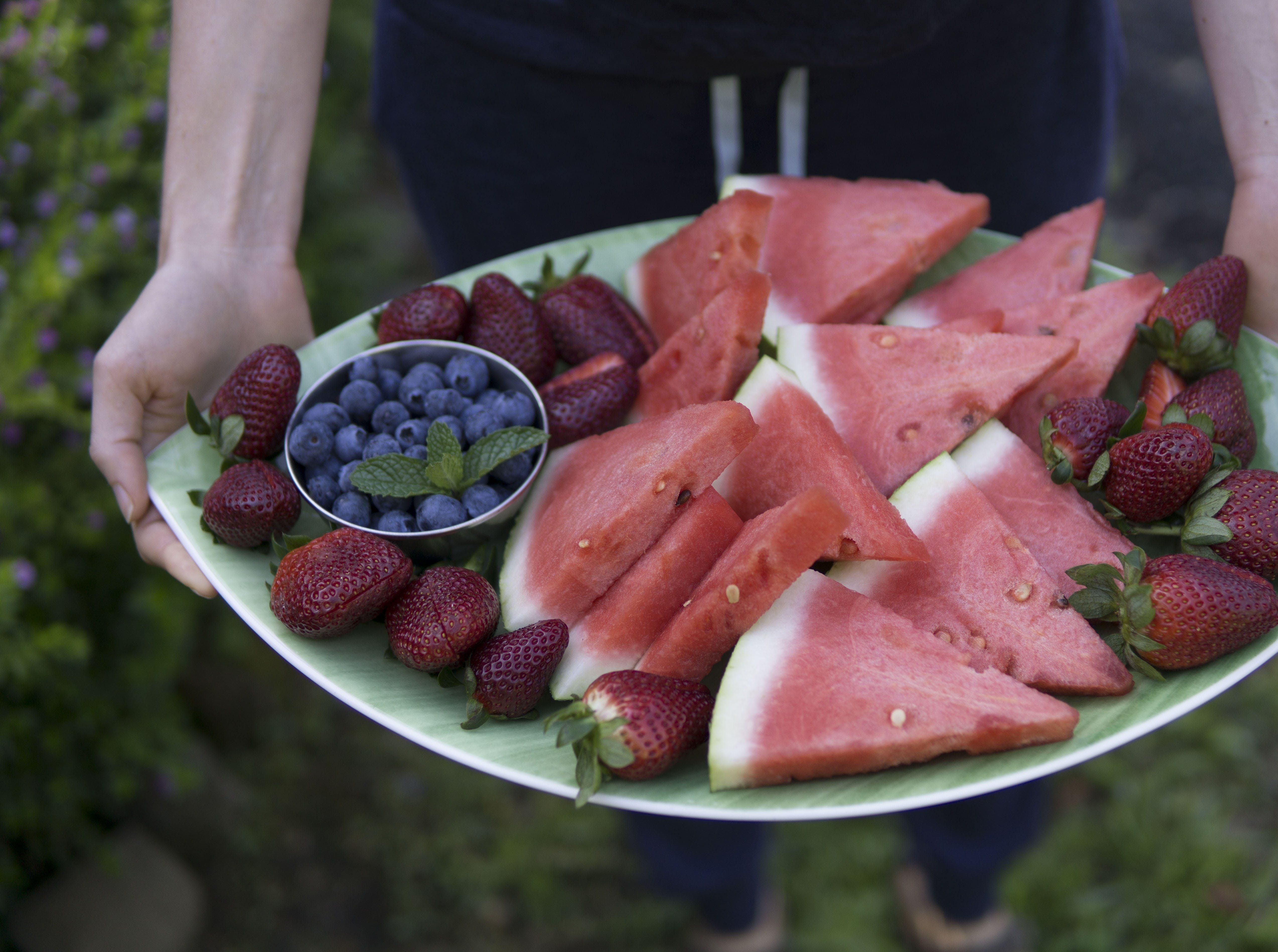 Person Holding Oval Green Plate Full Of Sliced Watermelons, Strawberries, And Blueberries