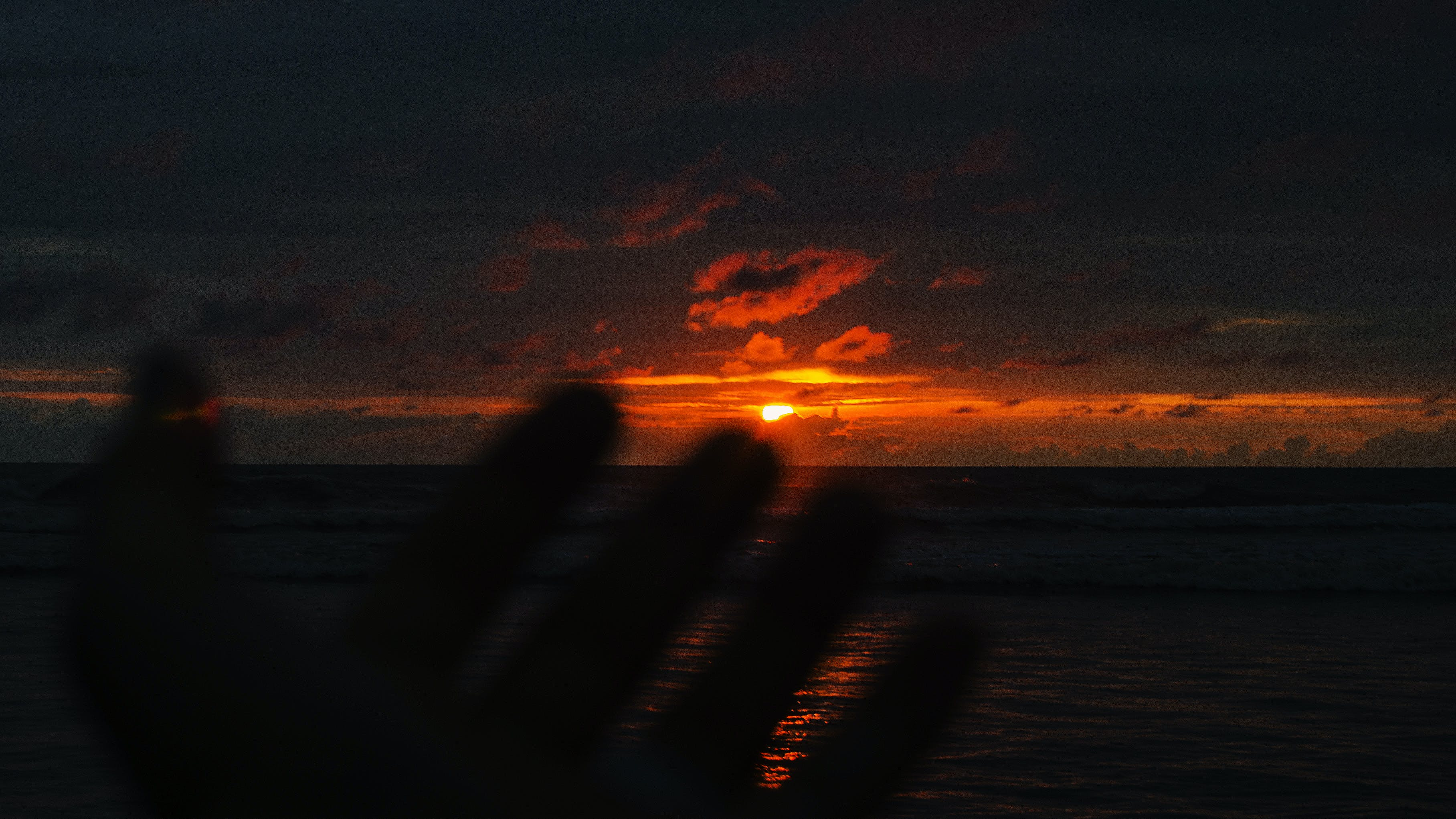 Person's Hand With Over-view of Sea at Golden Hour