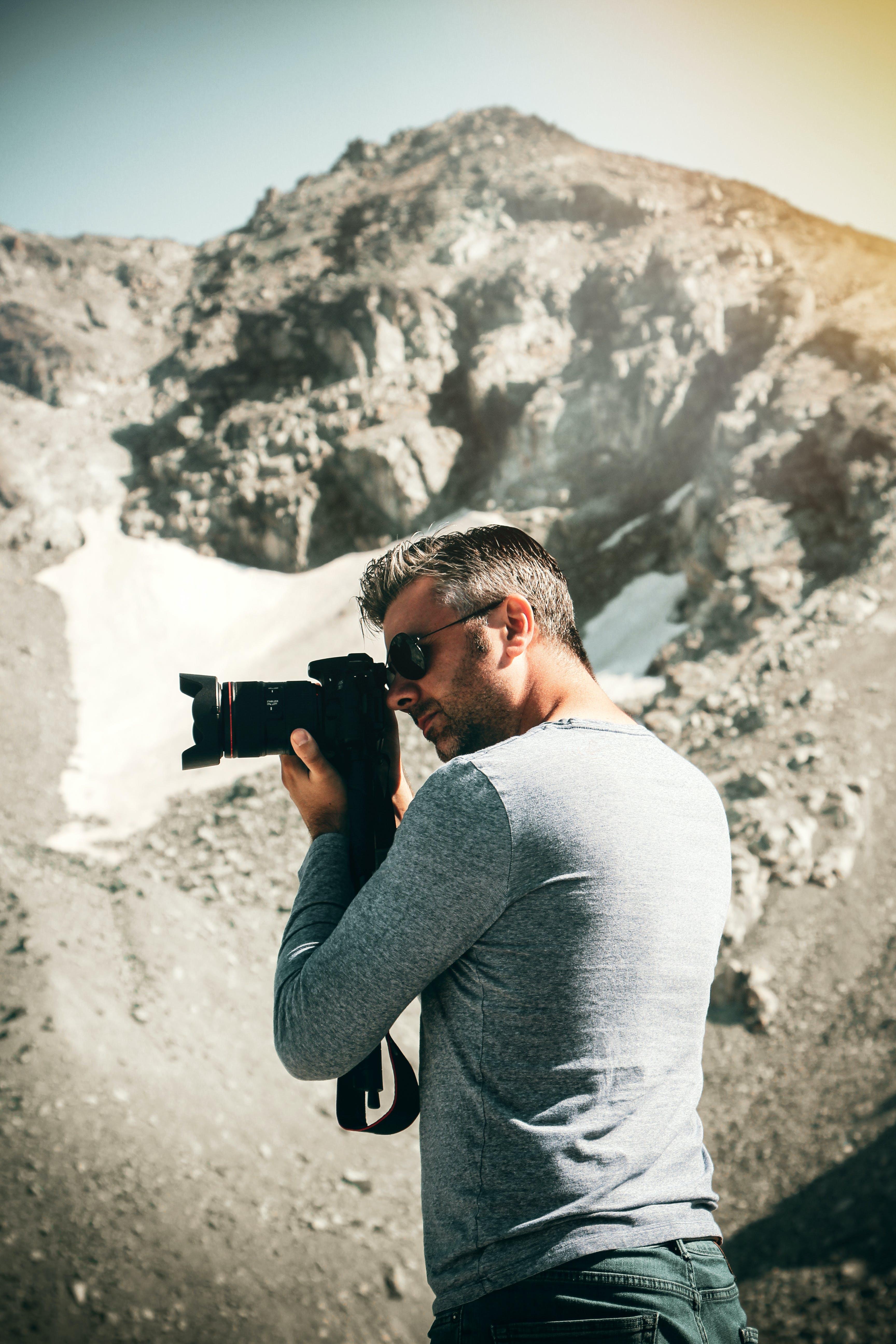Man Standing Taking Photo Near Mountain