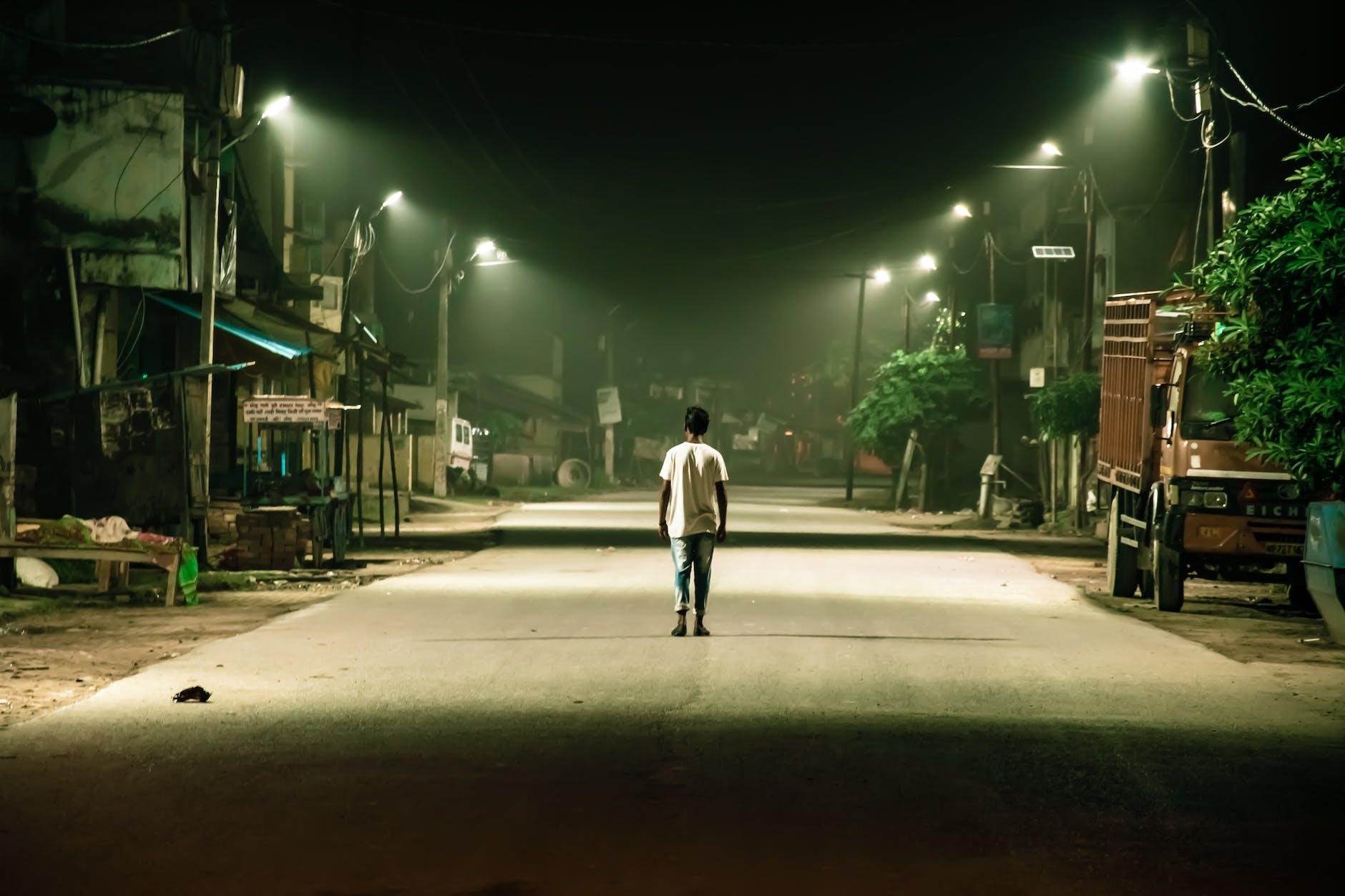 Man Wearing Crew-neck T-shirt Walking on Gray Pathway during Nighttime