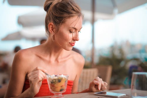 Woman Holding Silverware While Looking at Phone