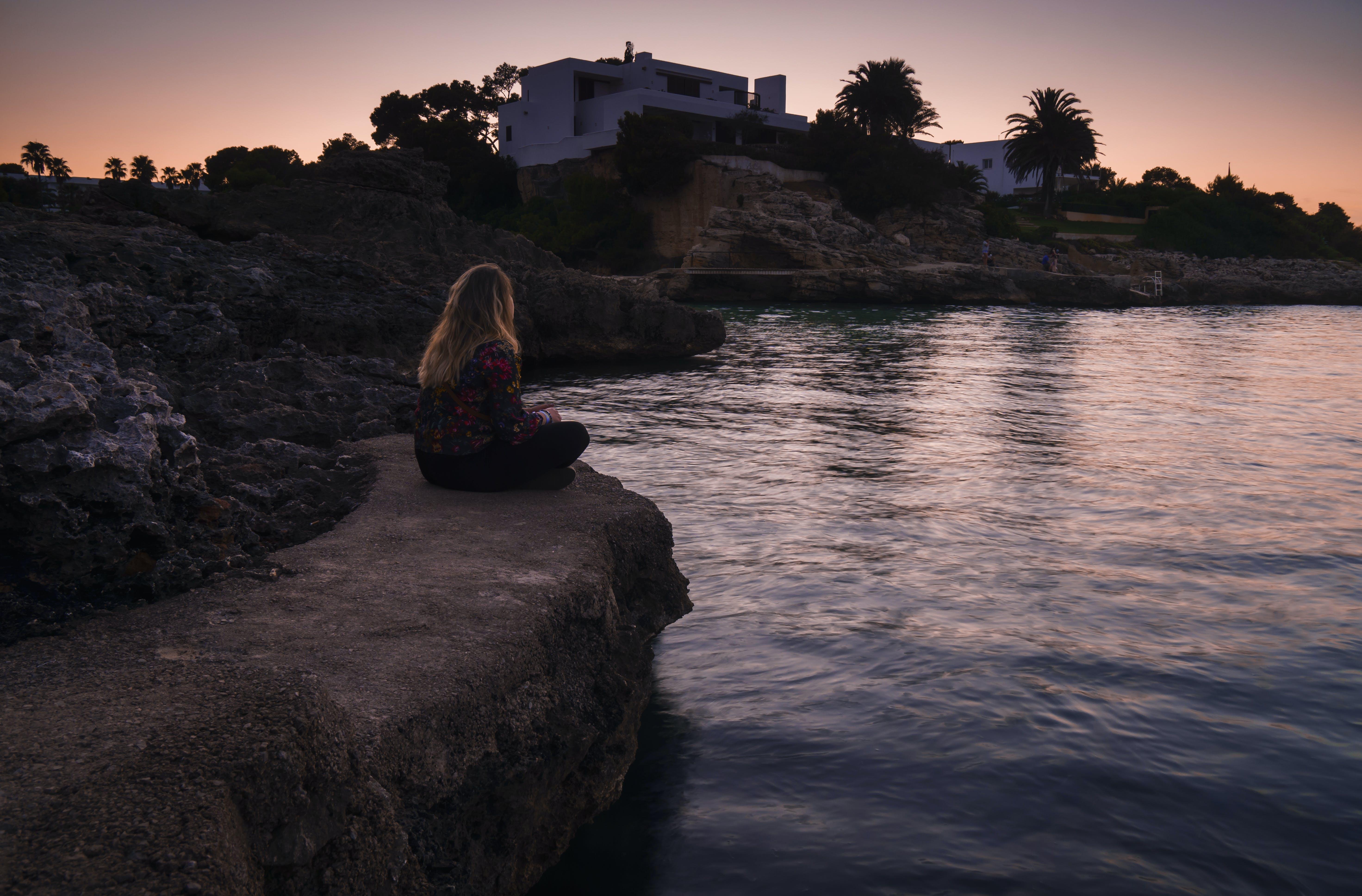 Woman Sitting on Edge of Rock Near Body of Water