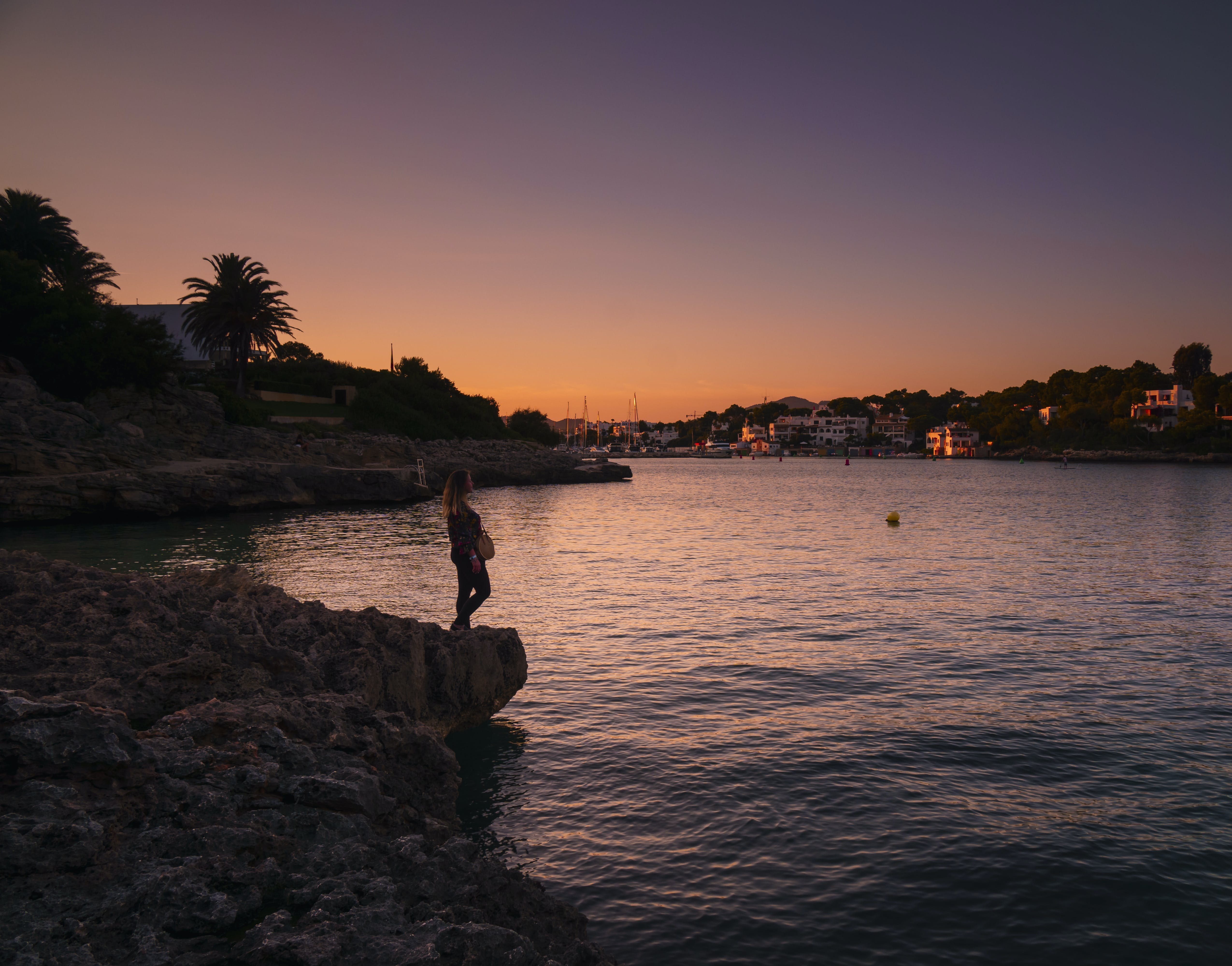 Woman Standing Near Body of Water at Night