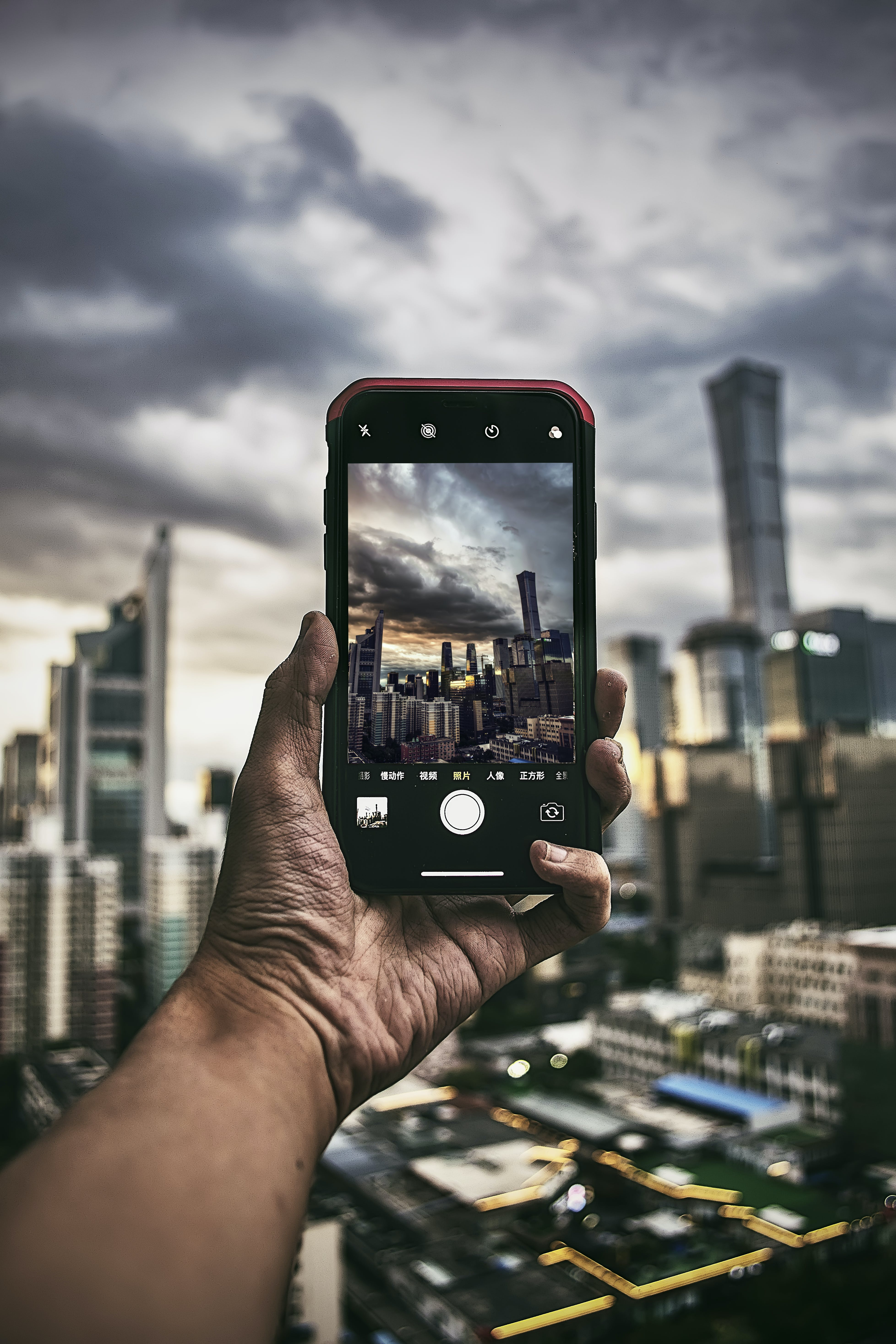 Person Taking Photo Of High Rise Buildings