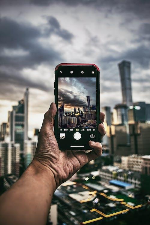 Kostnadsfri bild av byggnader, hand, skärm, smartphone