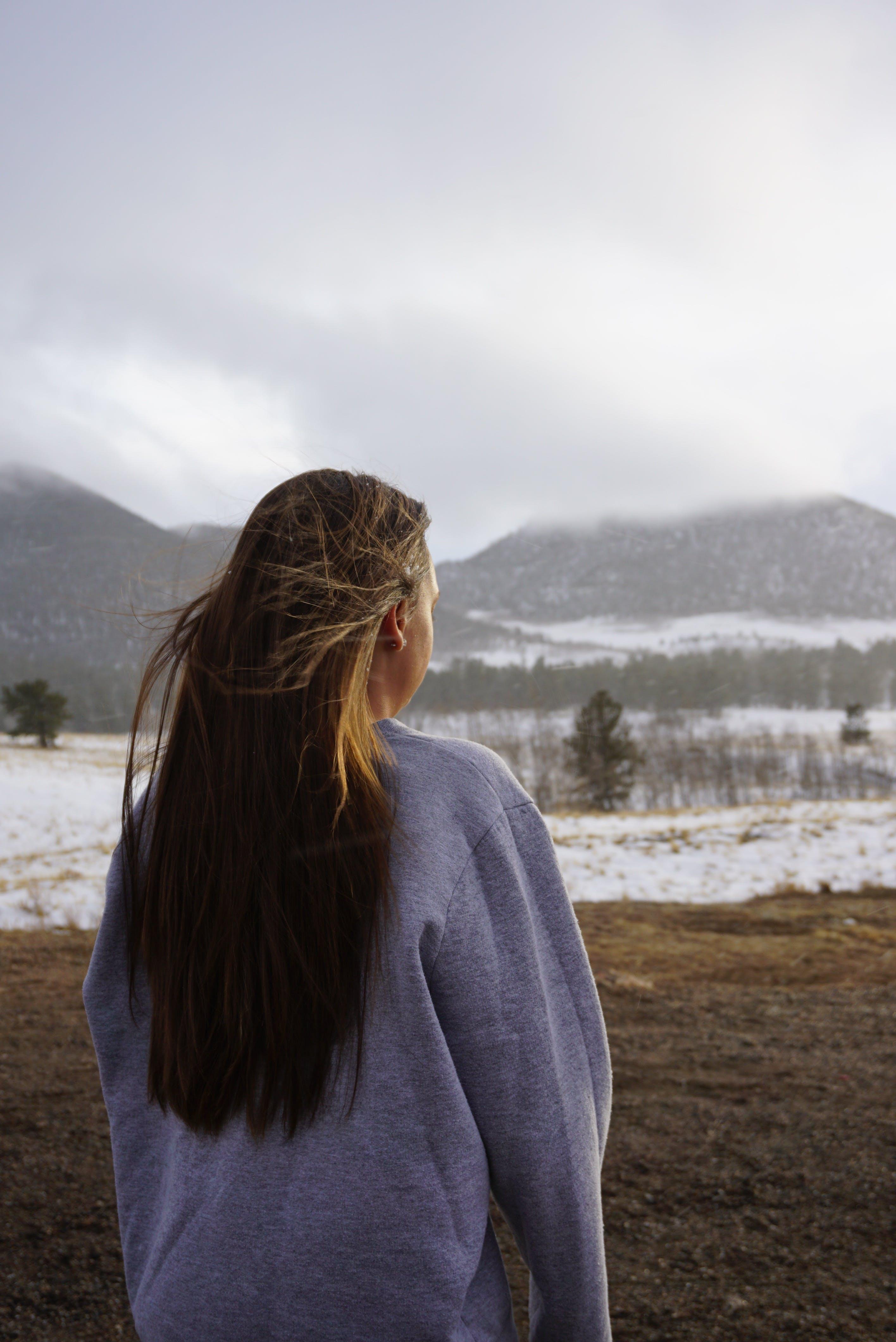 Woman in Gray Sweatshirt Standing on Grass Field