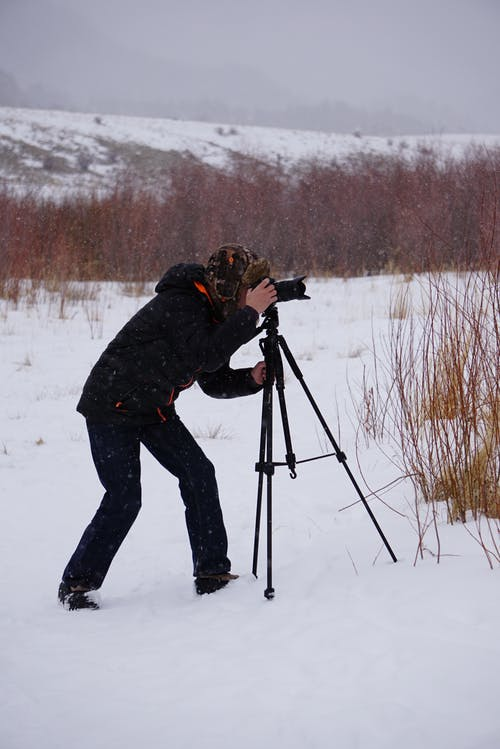Man Taking Photo in the Middle of Snow-covered Ground