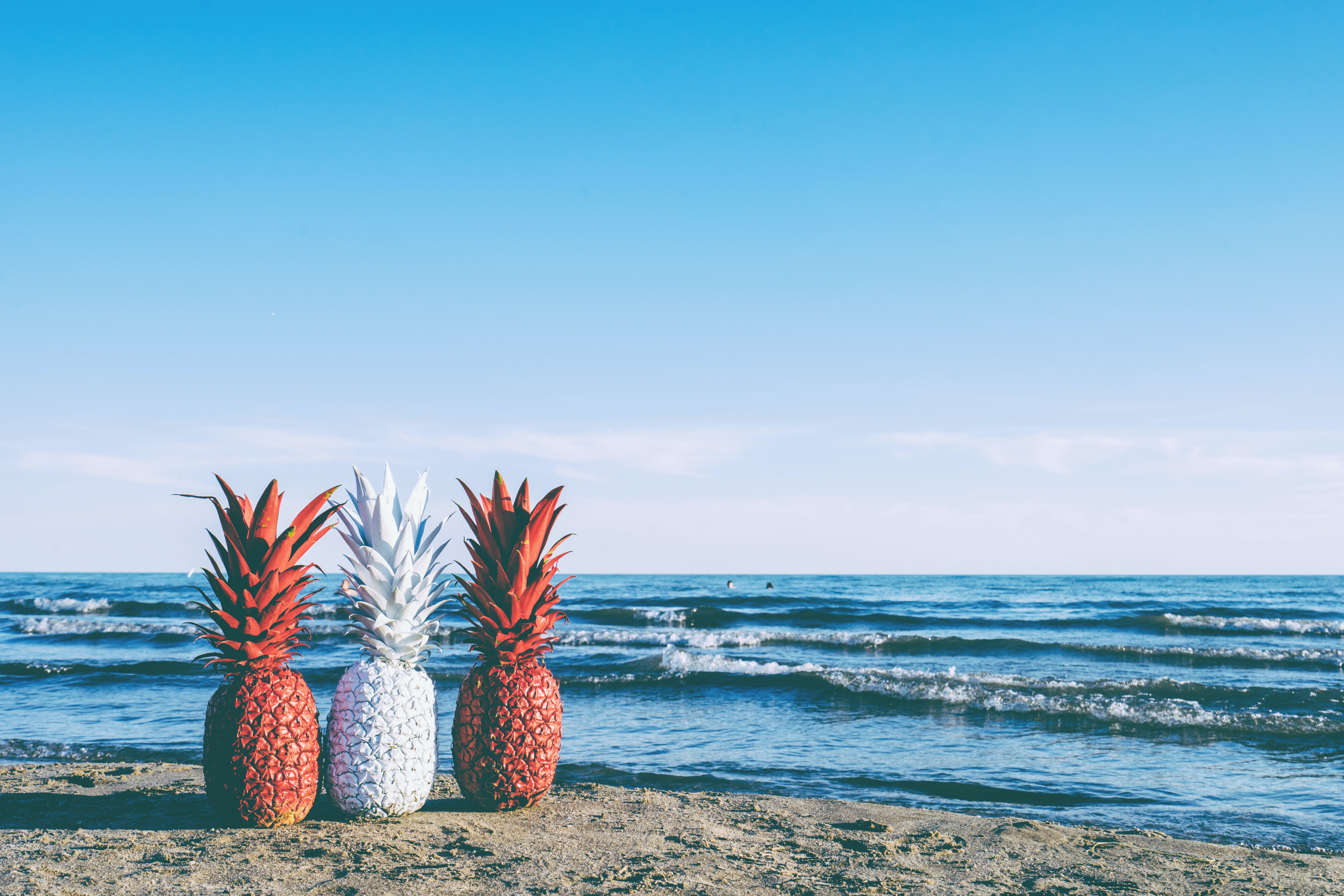 White and Two Red Painted Pineapples Near on Seashore